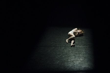 woman lying on a dark stage in the spotlight ocvering her face