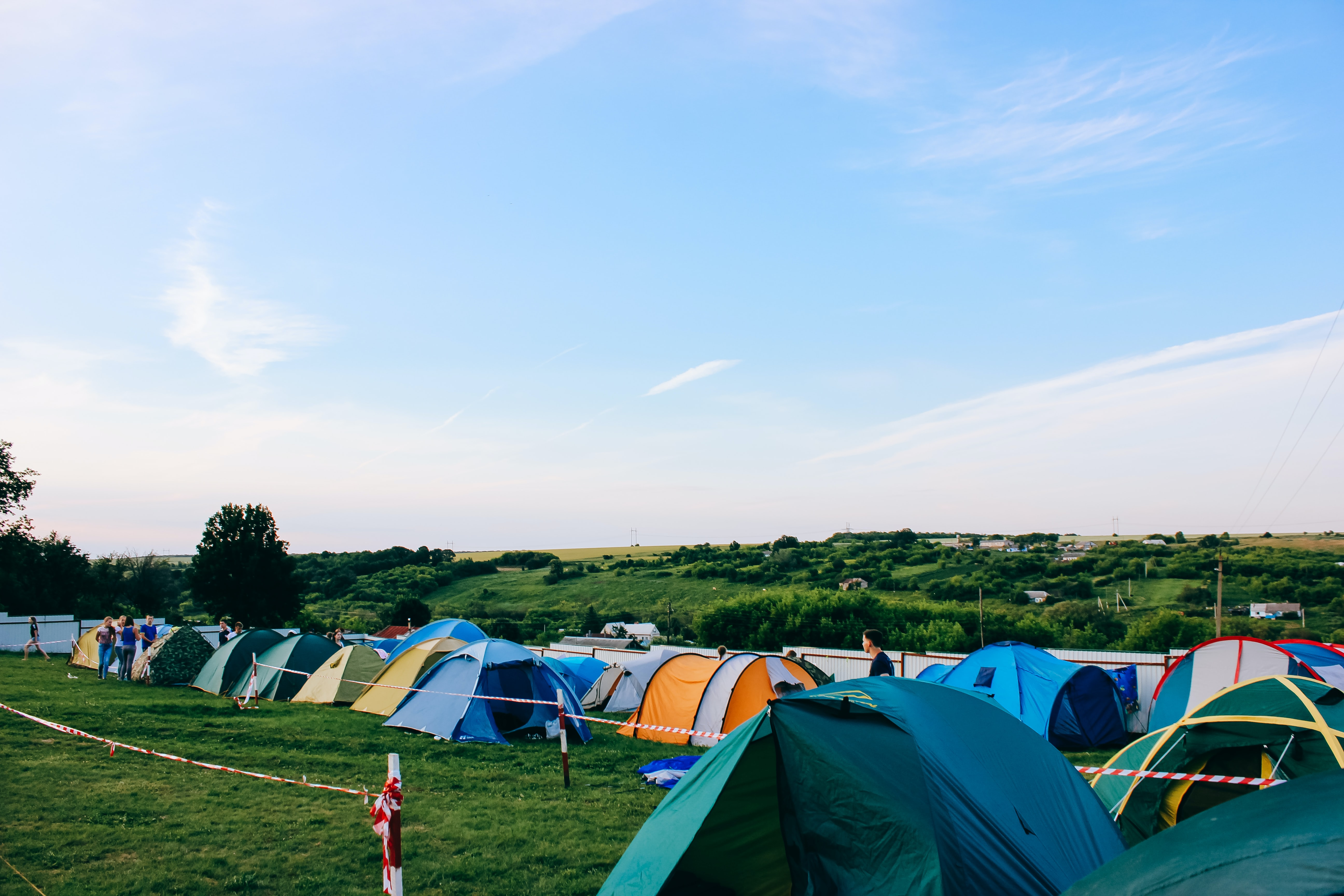 Colorful tents are pitched along a grassy field with a bright blue sky behind thing