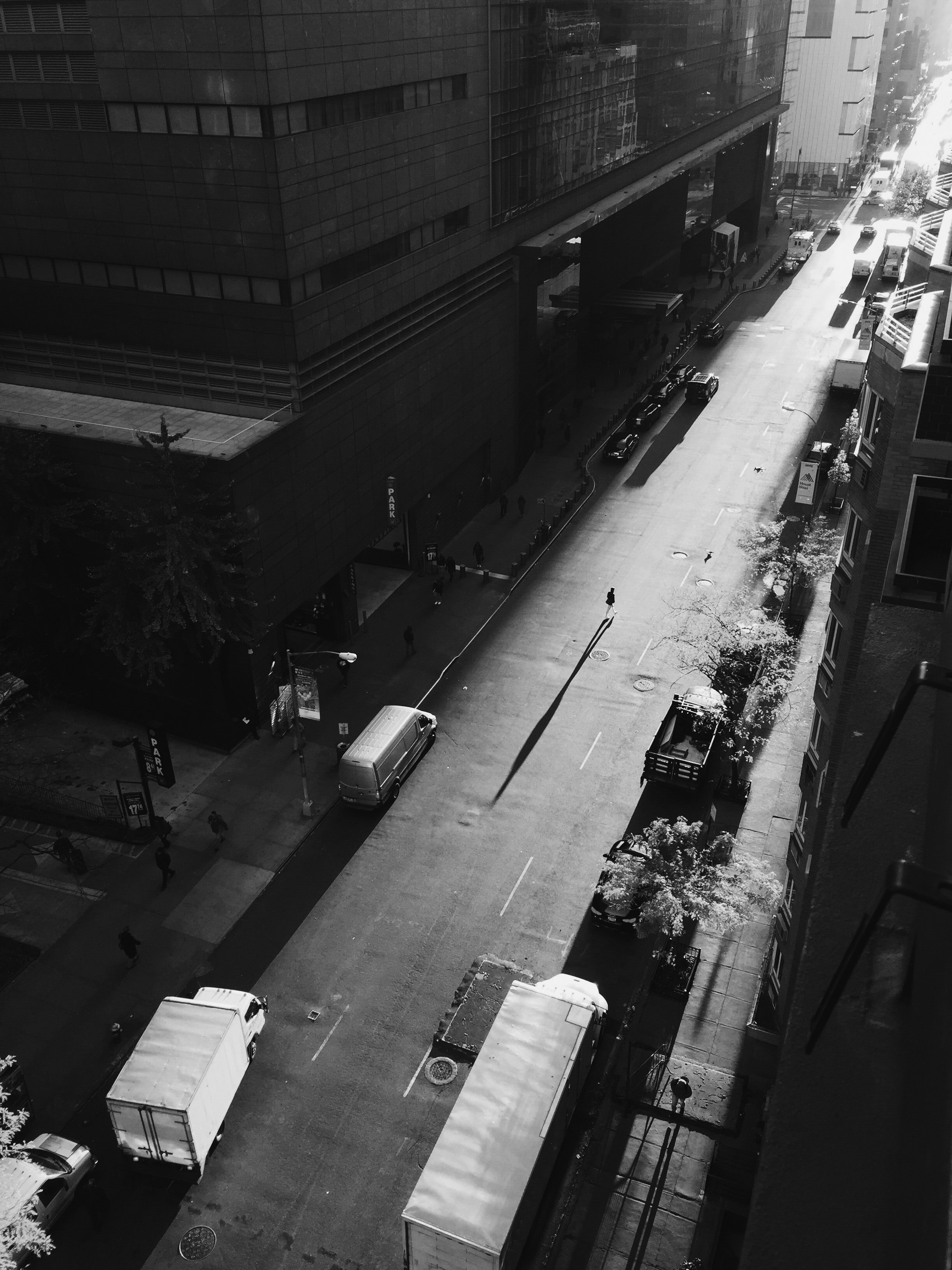 Black-and-white drone shot of pedestrians walking on shadowed street in New York