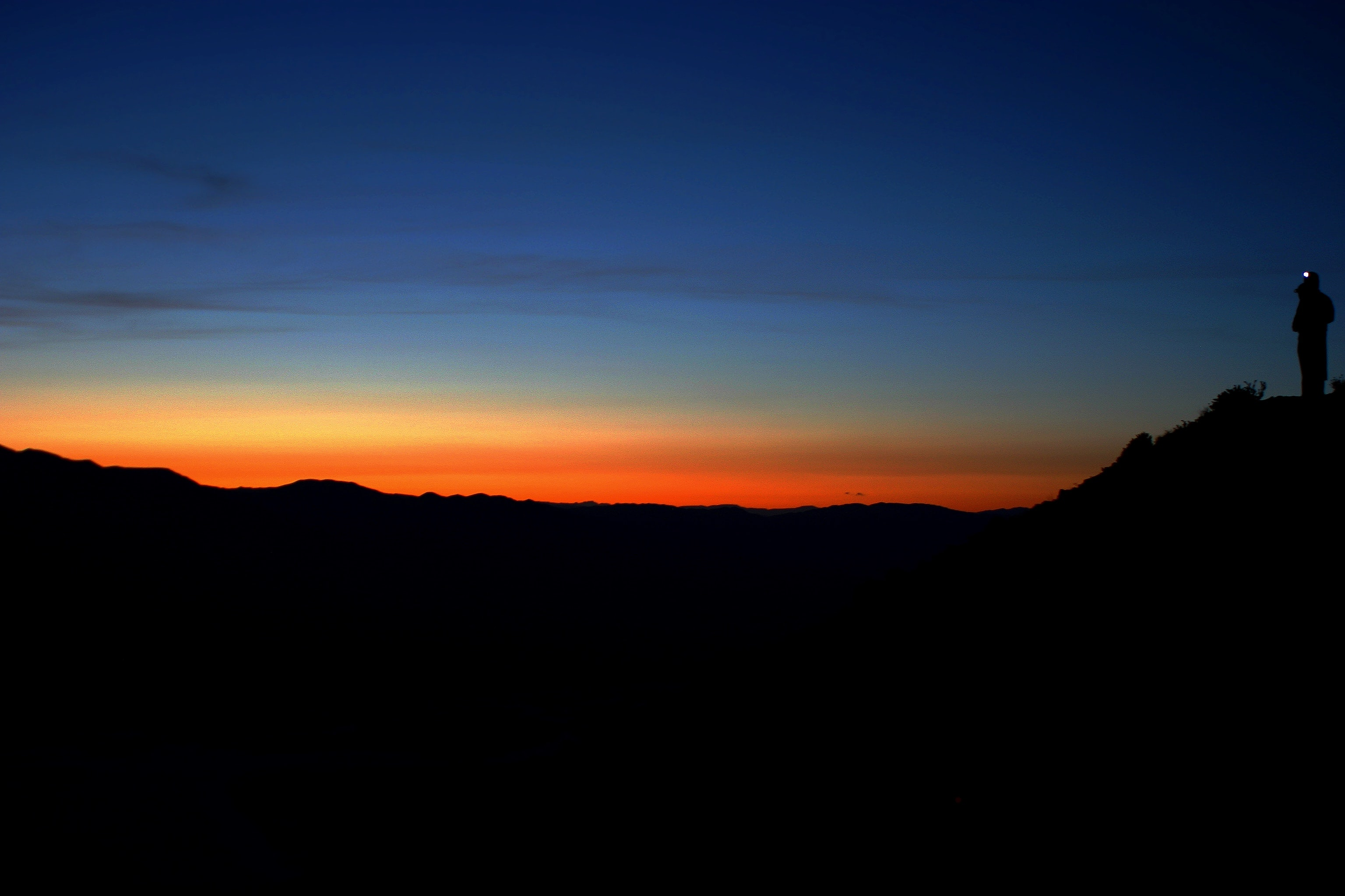 The sun rising along the horizon with a dark sky and silhouette of the skyline