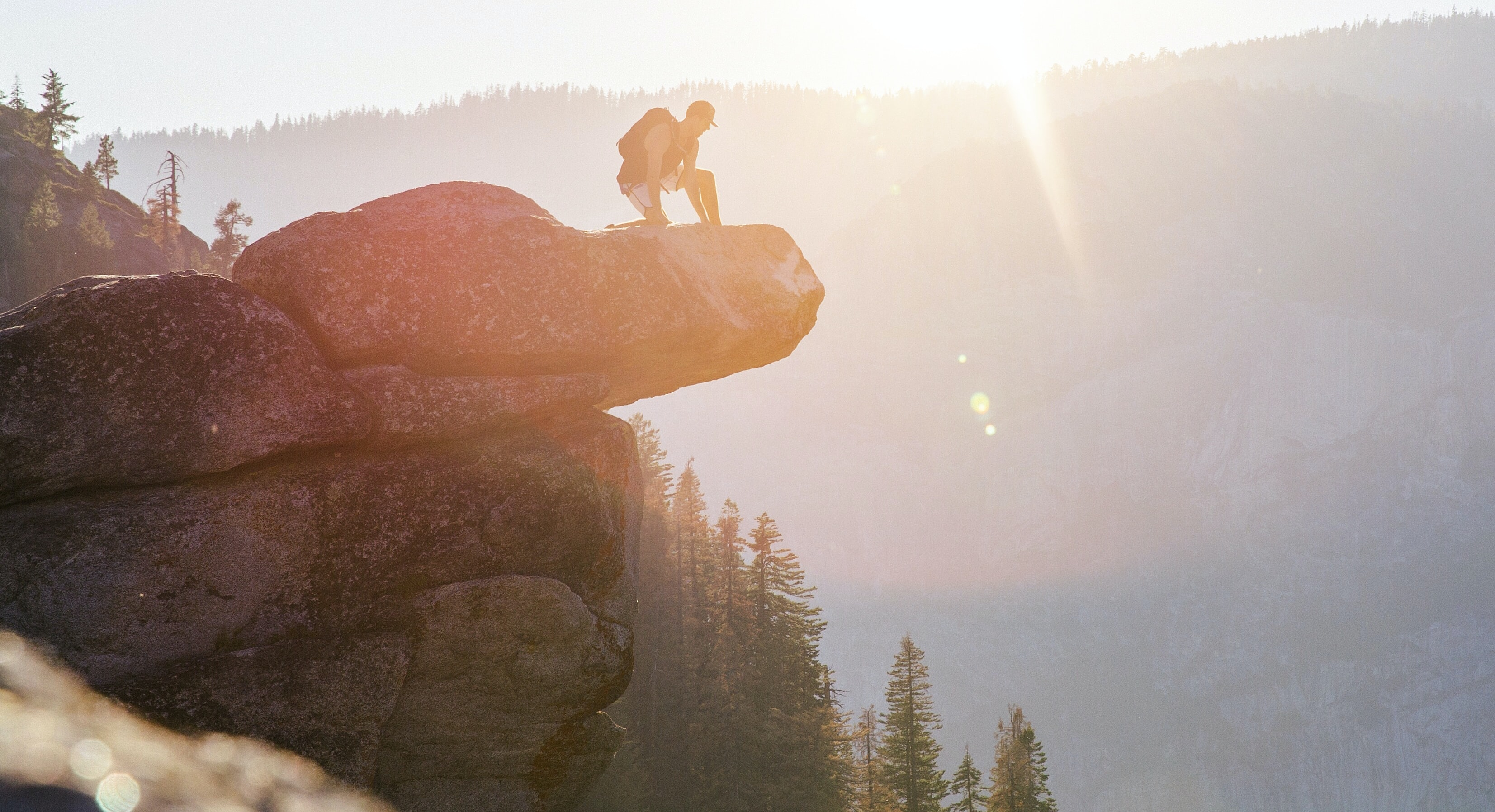 A person kneeling on the ledge of a rock with the sunset in the background at Glacier Point
