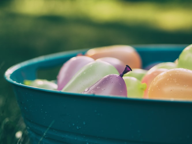 Multicolored water balloons in a bucket outdoors