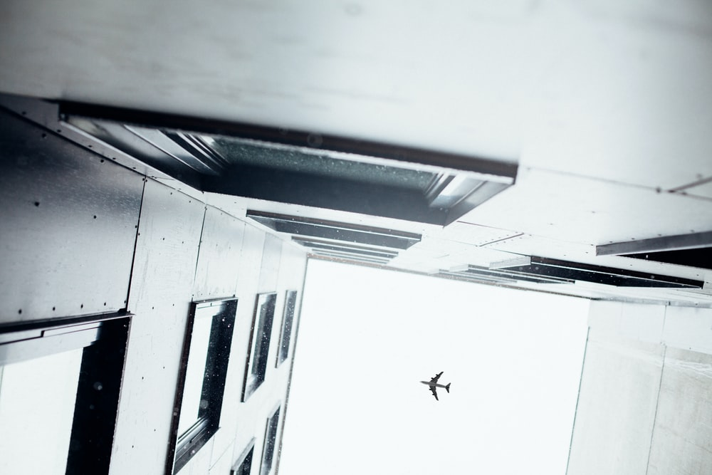 airplane above concrete building