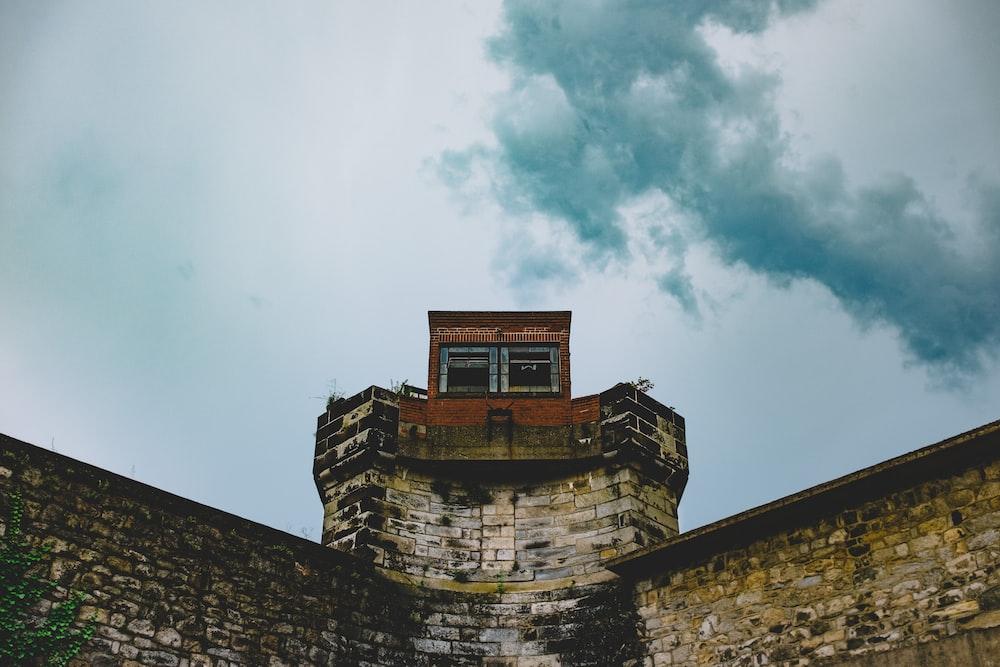 brown brick building under white clouds