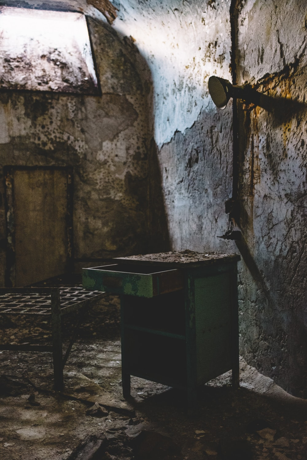 brown wooden table beside concrete wall