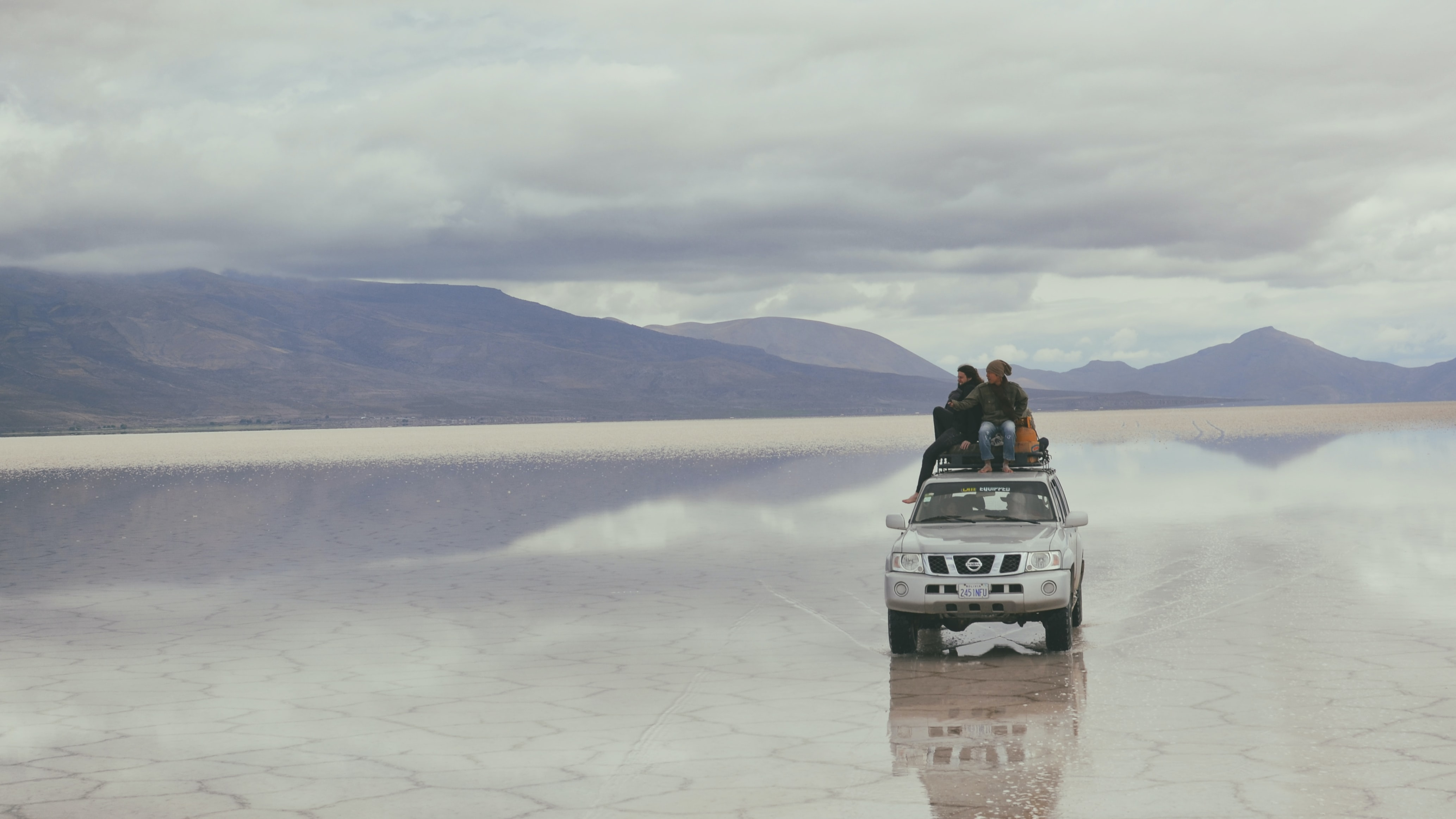 Two people sat on the roof of a silver Nissan jeep on a salt flat, Uyuni