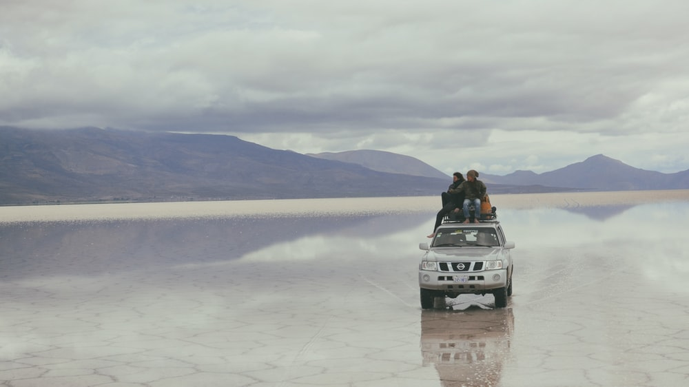 people on silver vehicle under gray sky during daytime