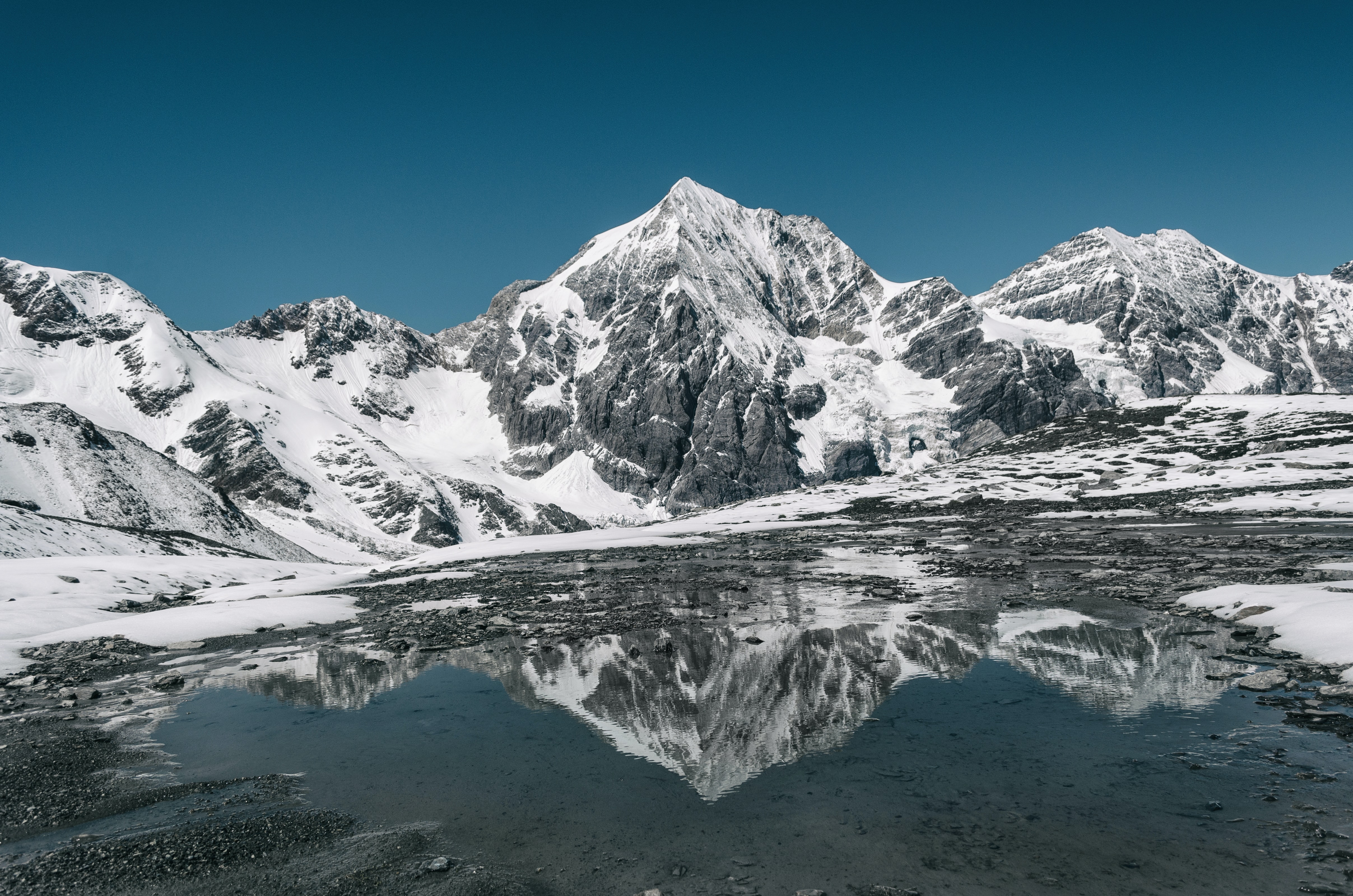 Snowy peaks of Ortler reflected in the icy water