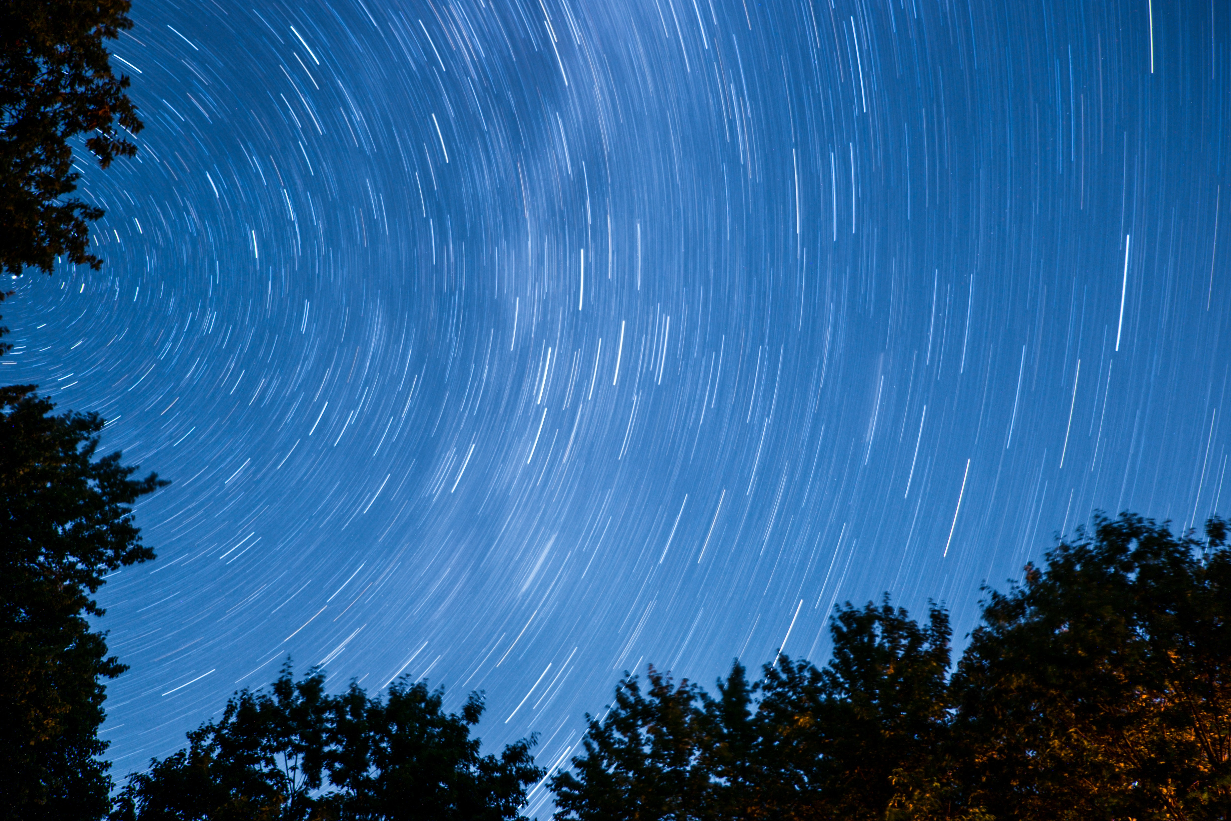 A blue night sky with star light trails above Fryeburg in the state of Maine