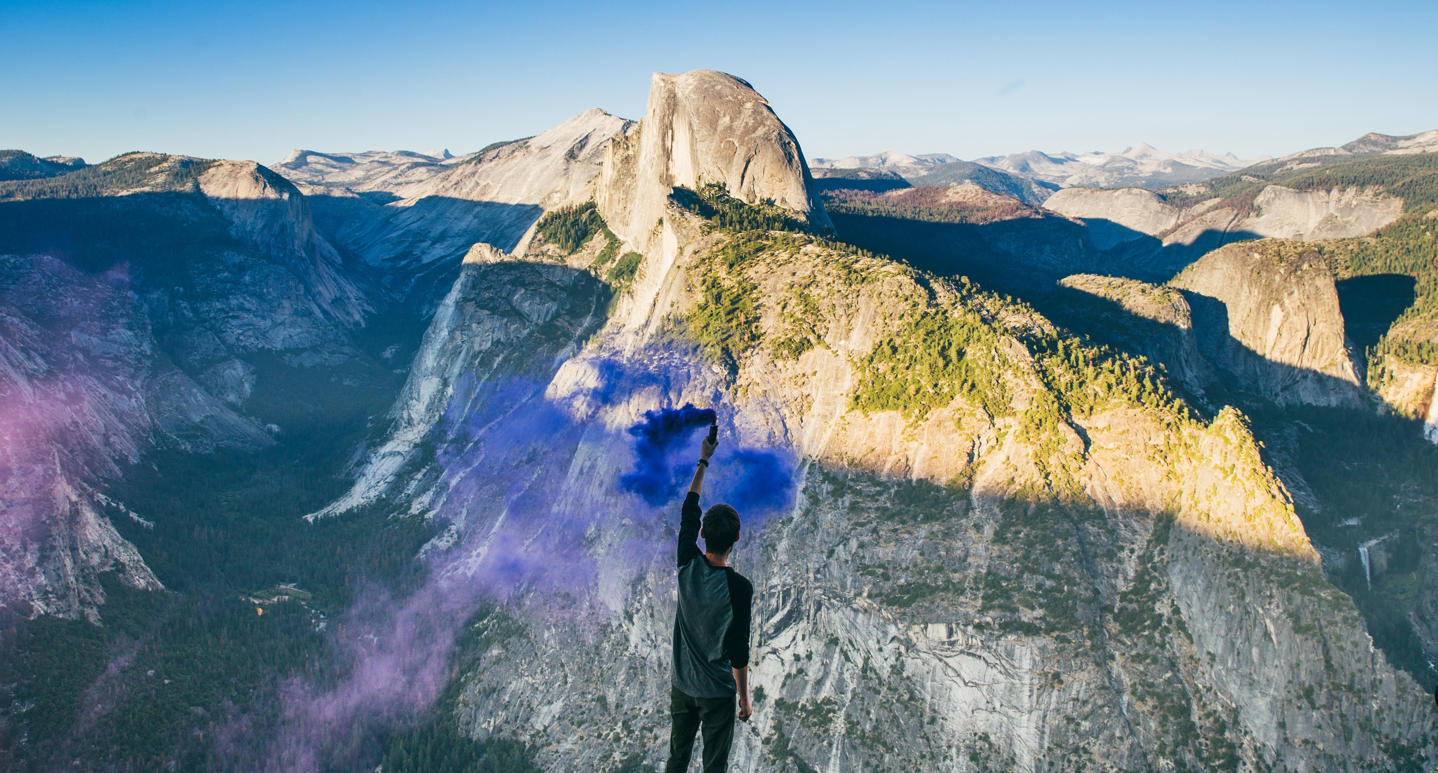 person wearing gray shirt facing gray mountain