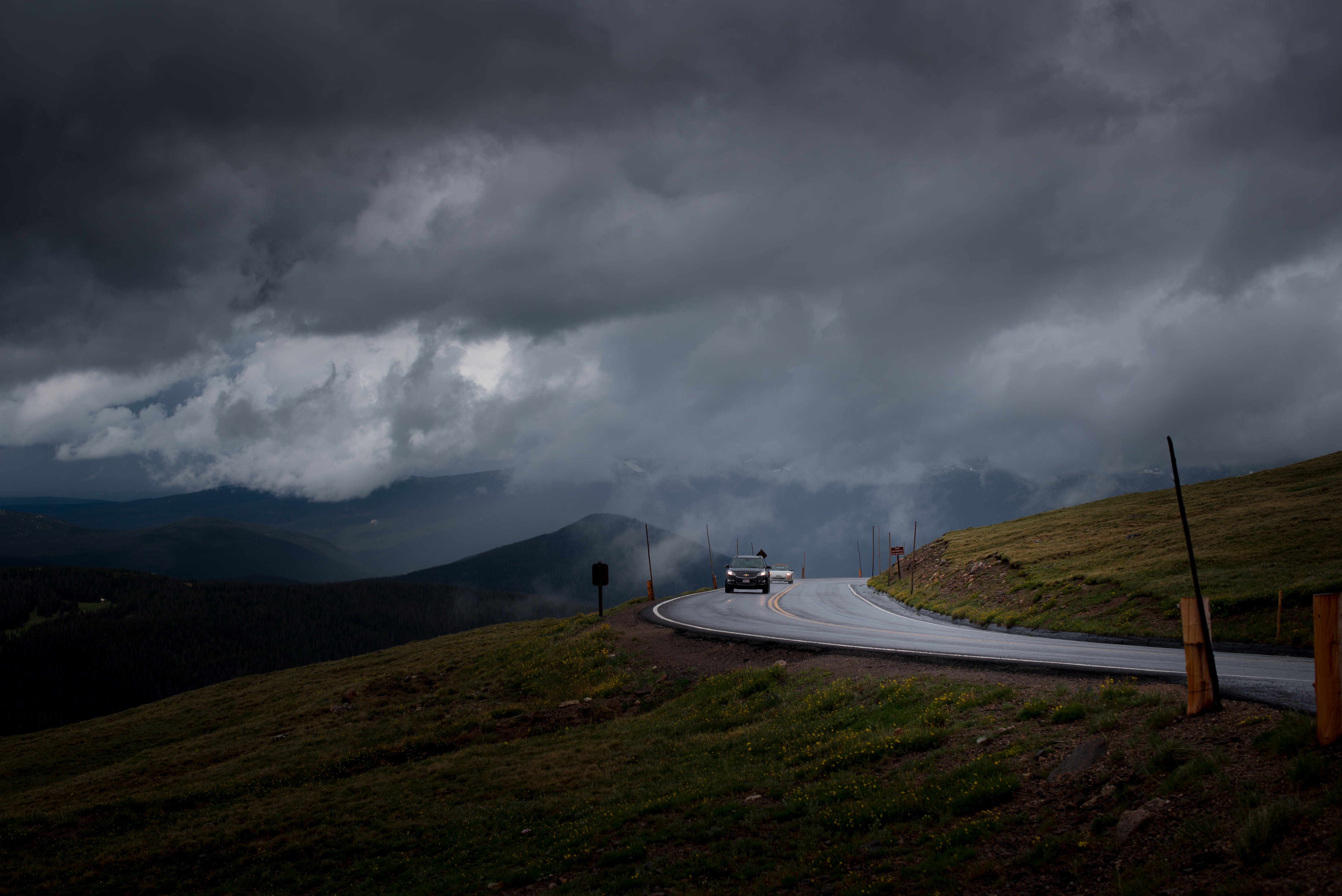 Cars on a curve in a road along a green hill on a cloudy day