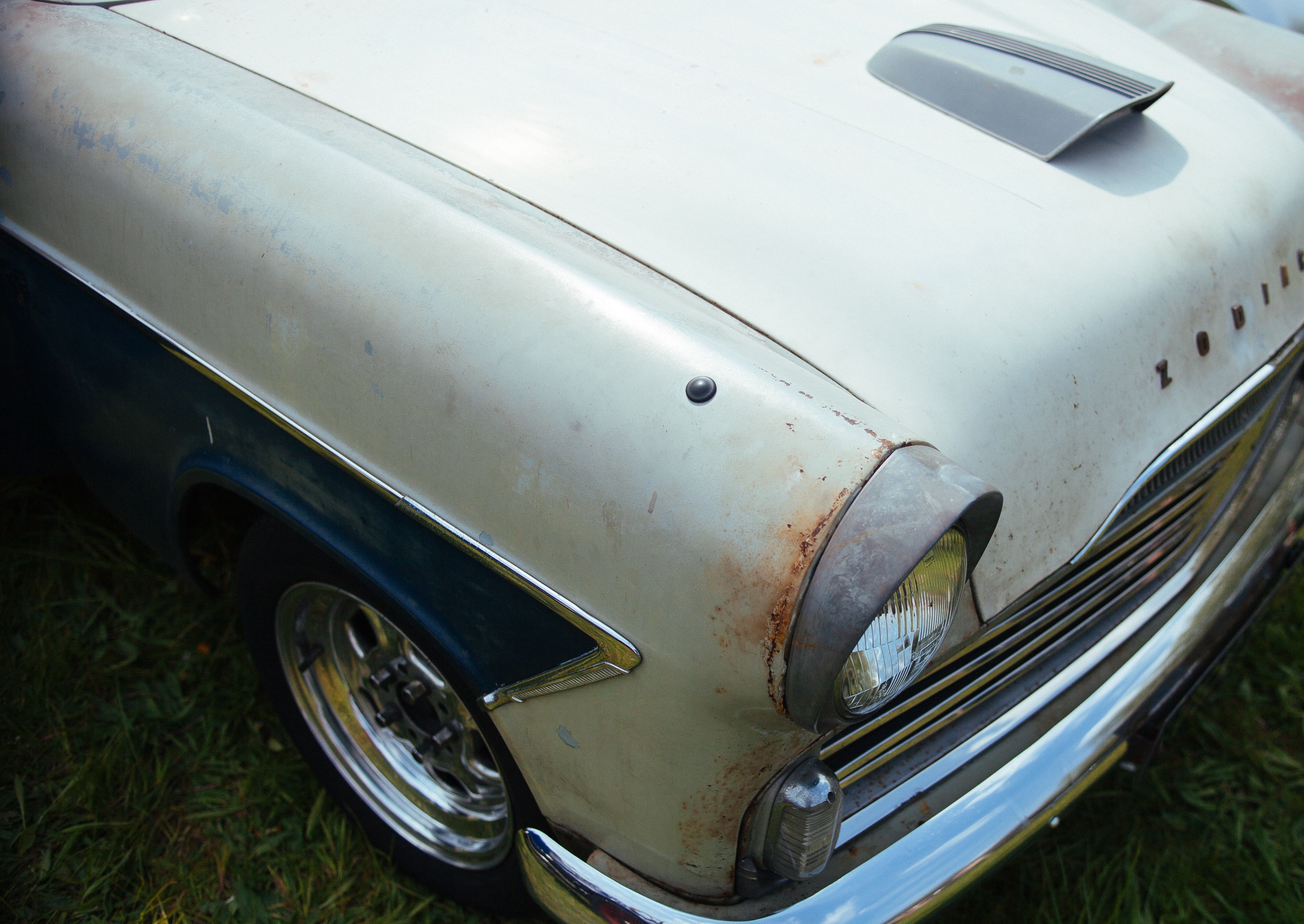 A rusty white vintage car.