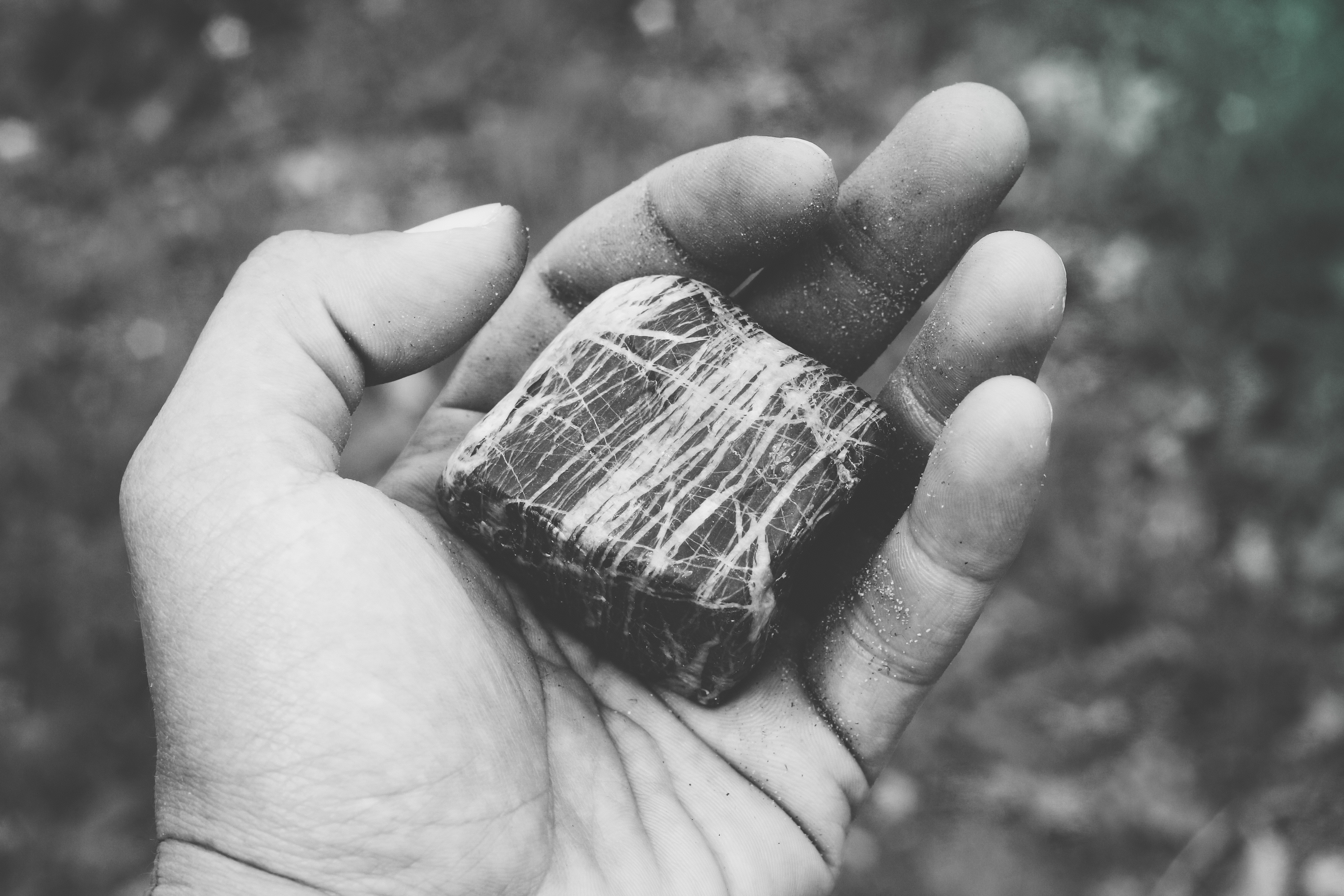 A black-and-white photo of a person's hand holding a cube-shaped rock