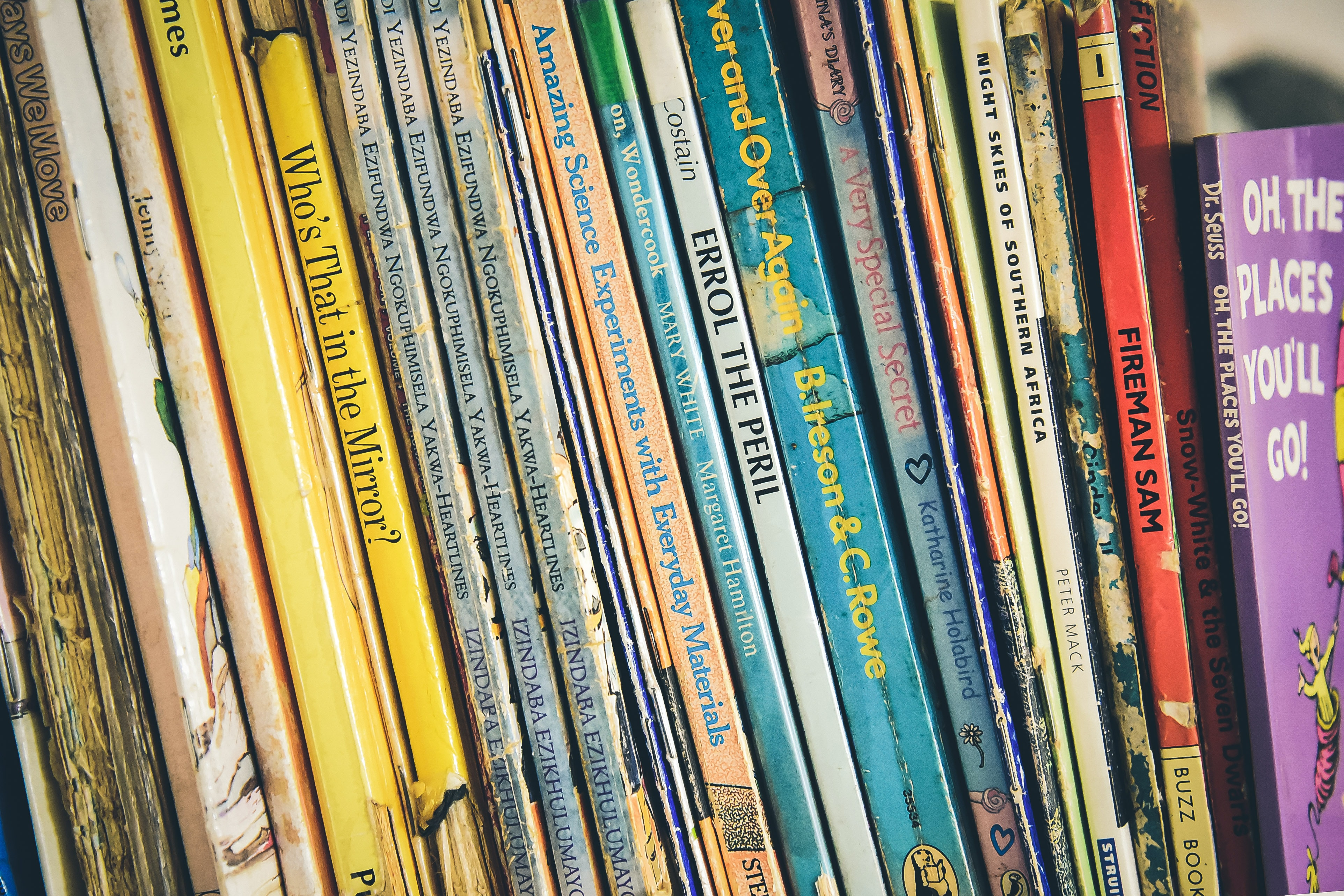 Several children's books on a shelf