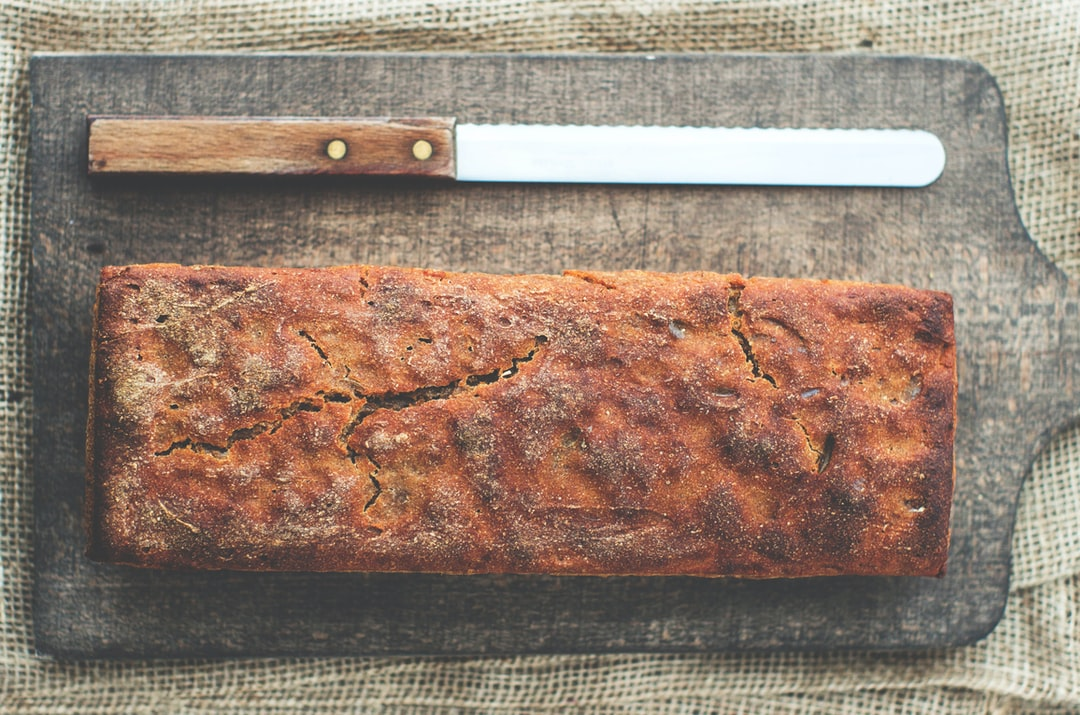 Freshly baked bread on a cutting board with a bread knife
