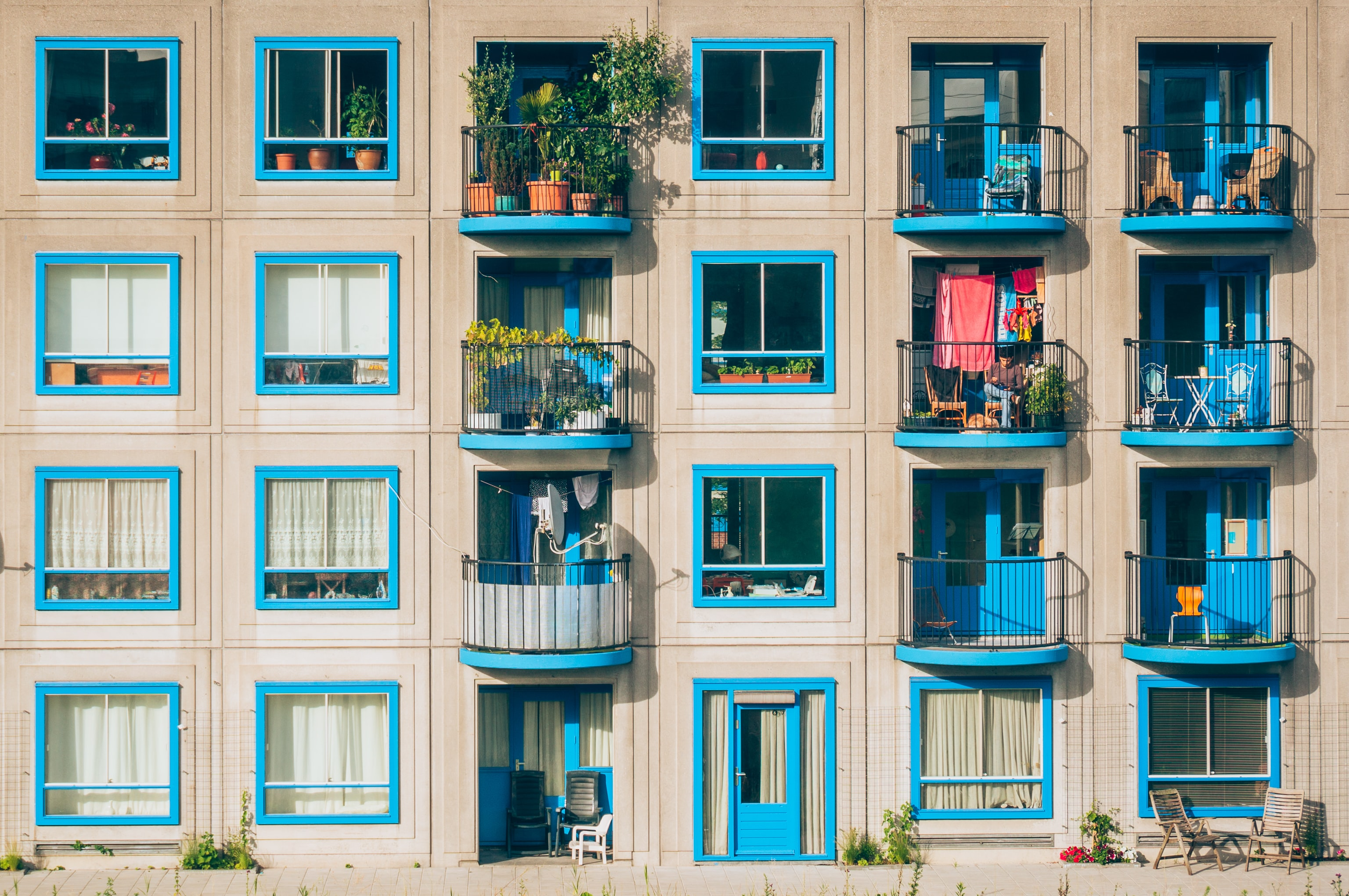 An apartment building with blue windows and balconies filled with plants in Amsterdam, Bullewijk