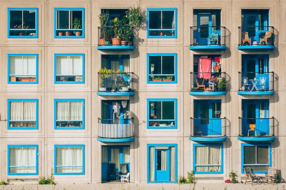white and blue concrete 4-storey building