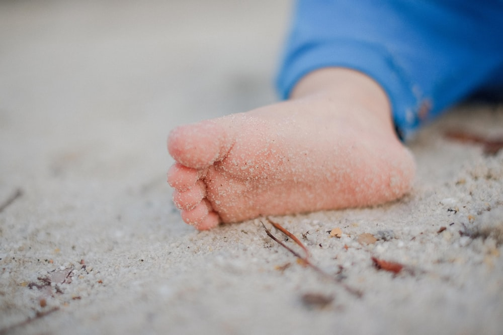 shallow focus photography of toddler's foot with sand