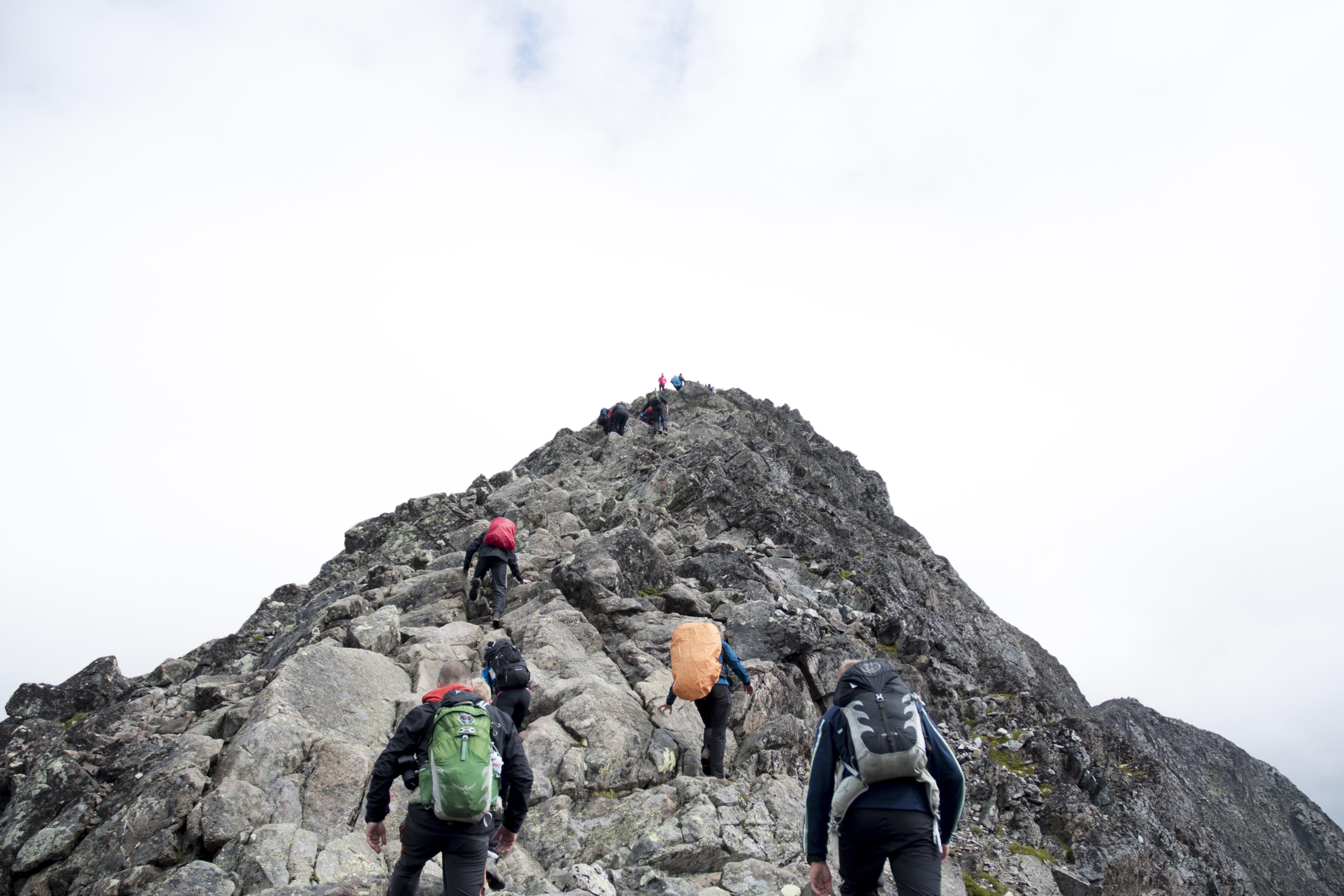 Hikers with backpacks summiting peaks of mountain