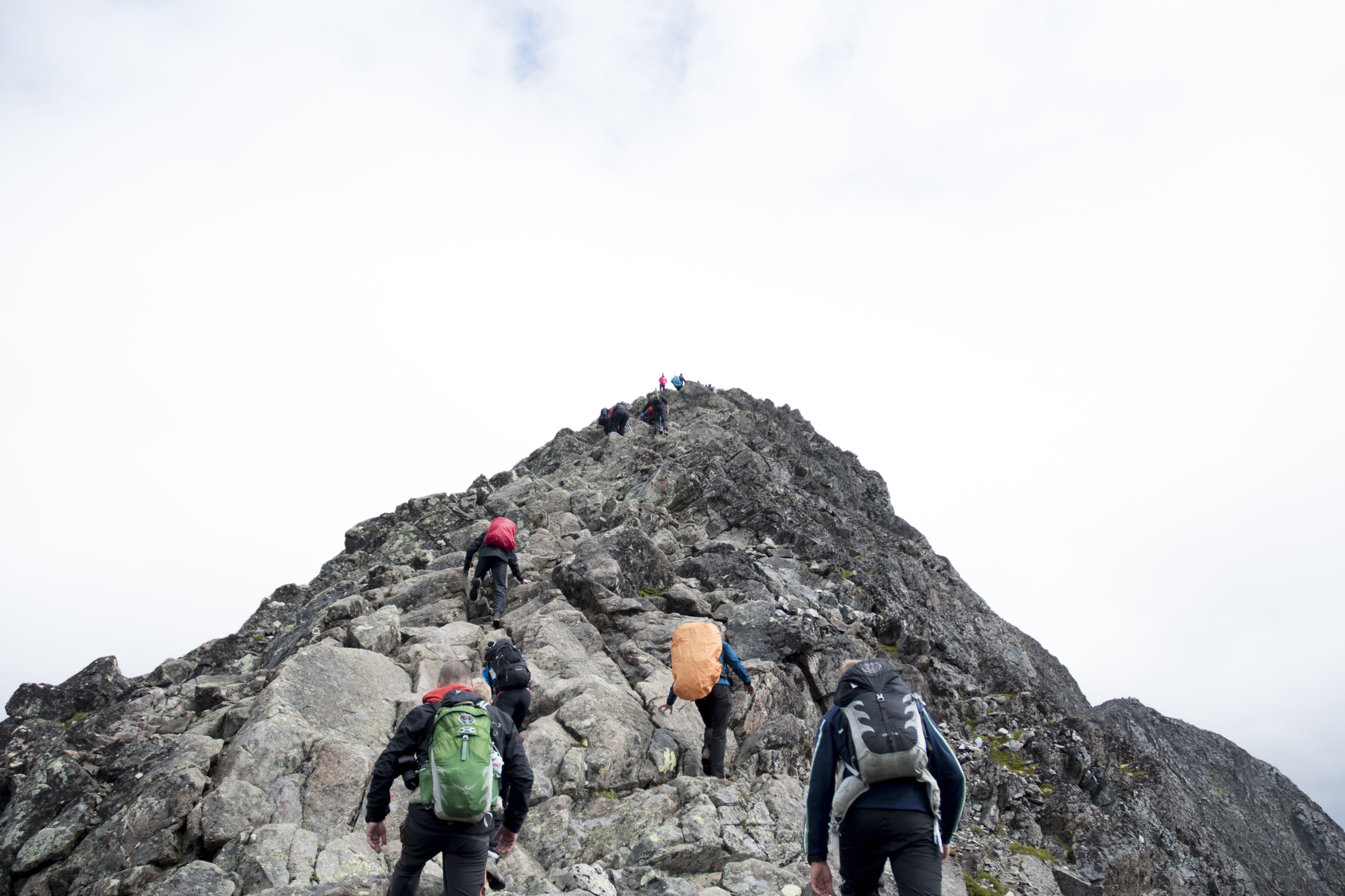 Hikers with backpacks summiting peaks of mountain