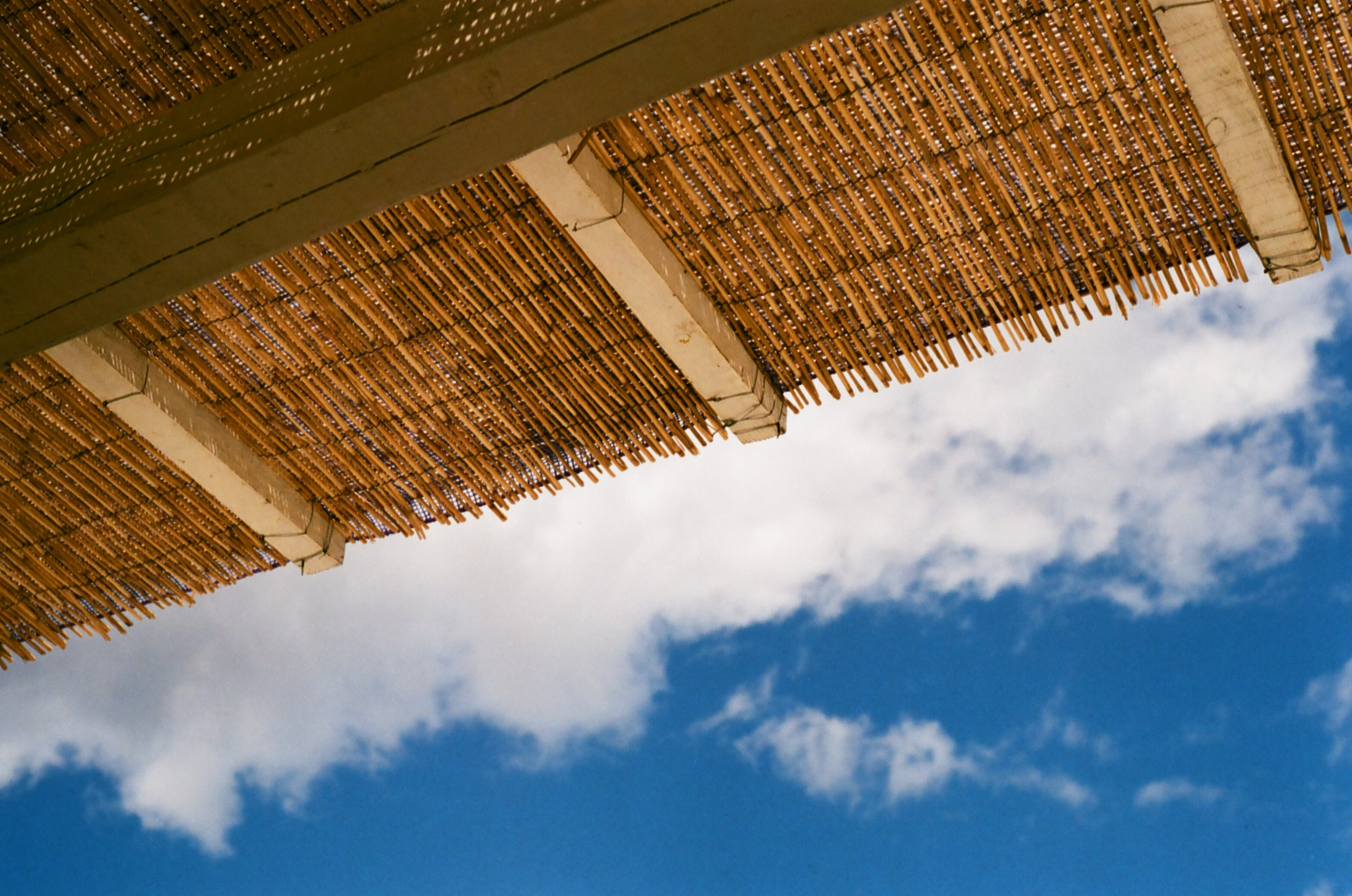 brown straw roof with brown wooden exposed beams under blue sky and white clouds at daytime