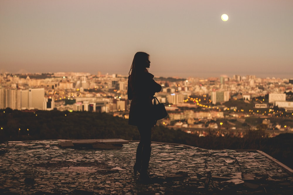 silhouette of woman standing during golden hour photography