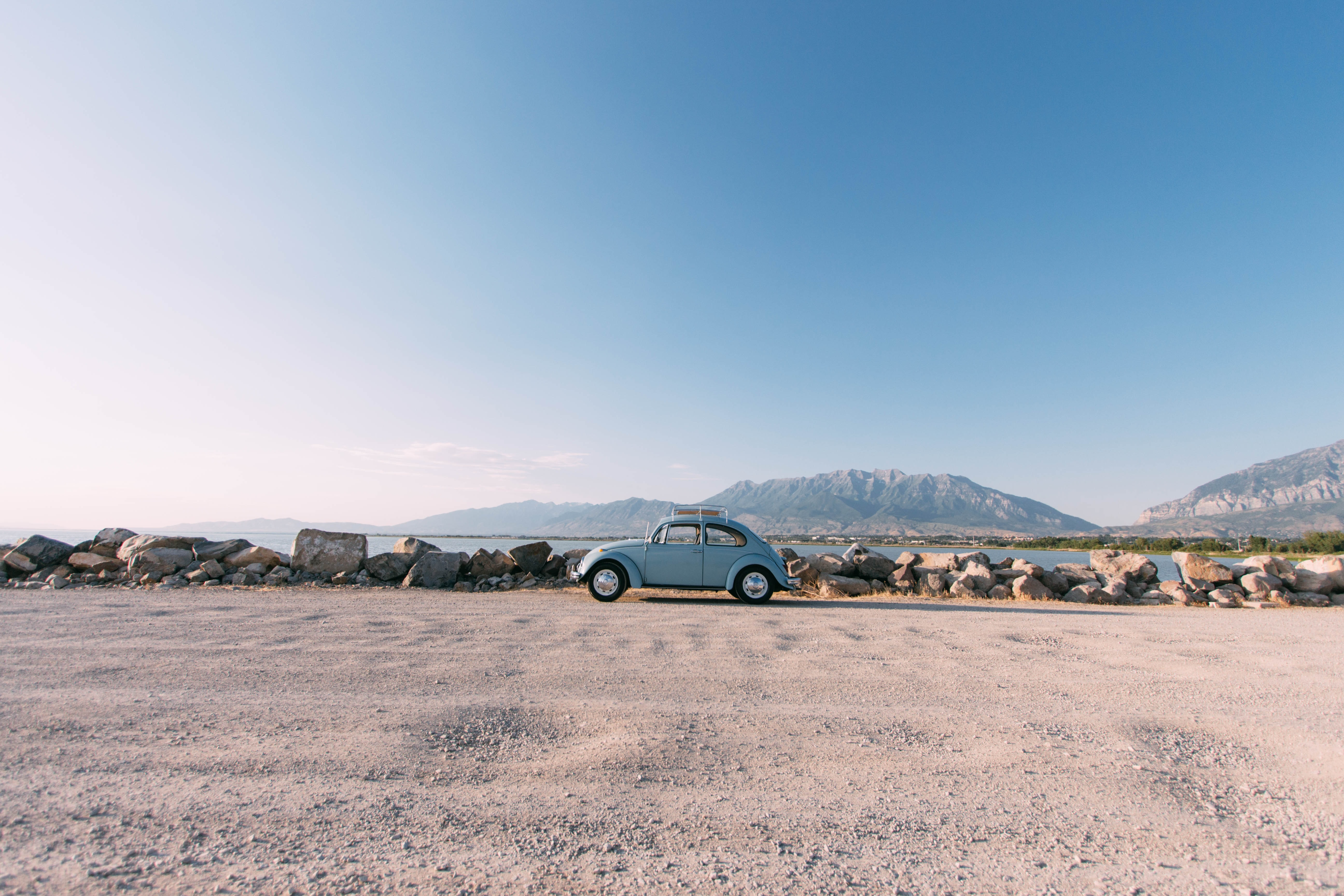 Vintage, blue Volkswagen Beetle parked on road in front of lake with mountains in the distance