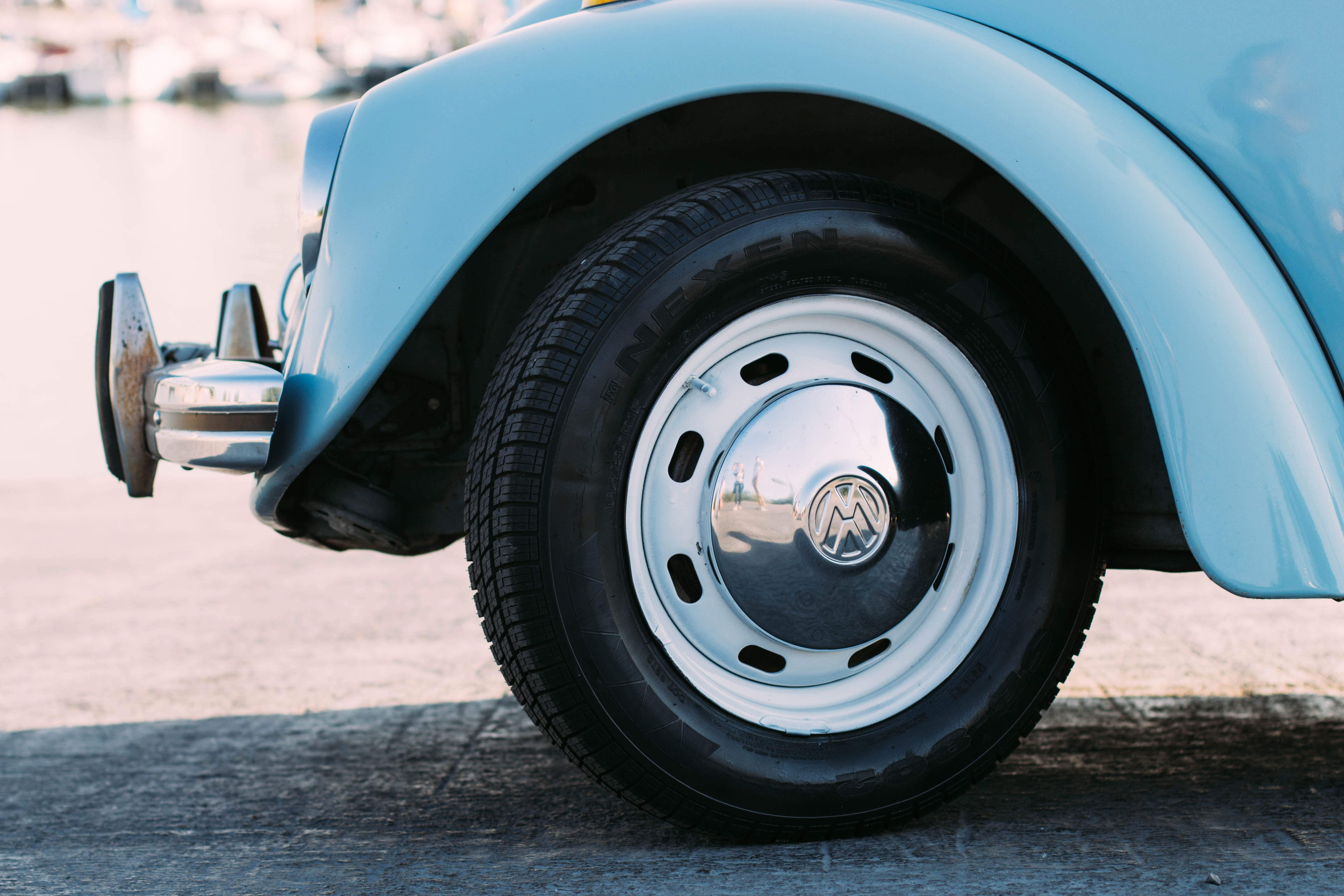 Front of Volkswagen blue car with logo on hubcap
