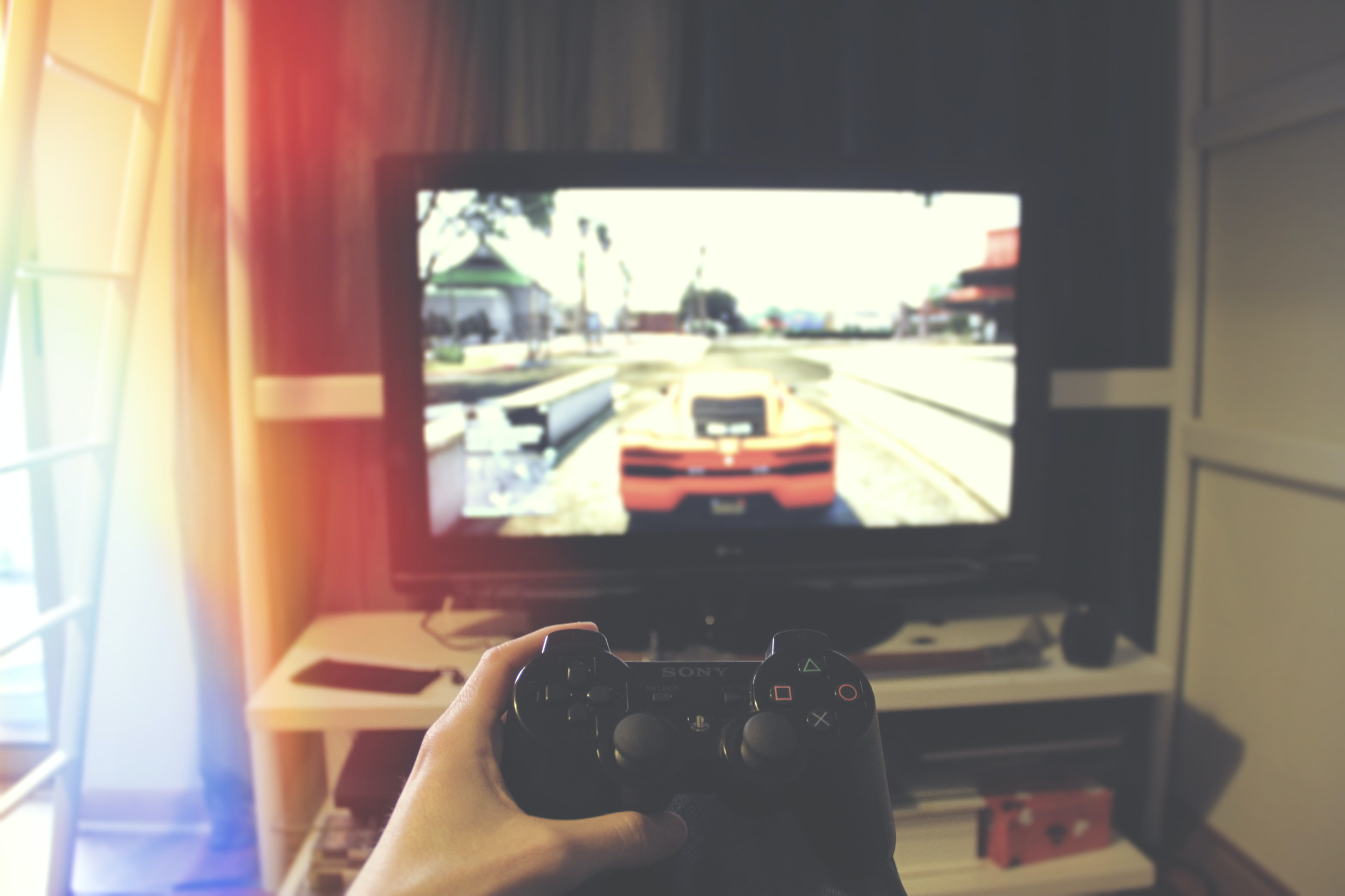 person holding Sony PS3 controller in front of flat screen monitor
