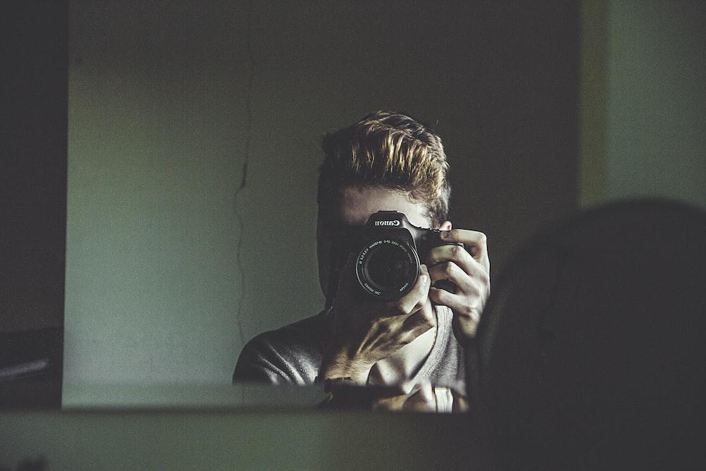 man taking photo on mirror