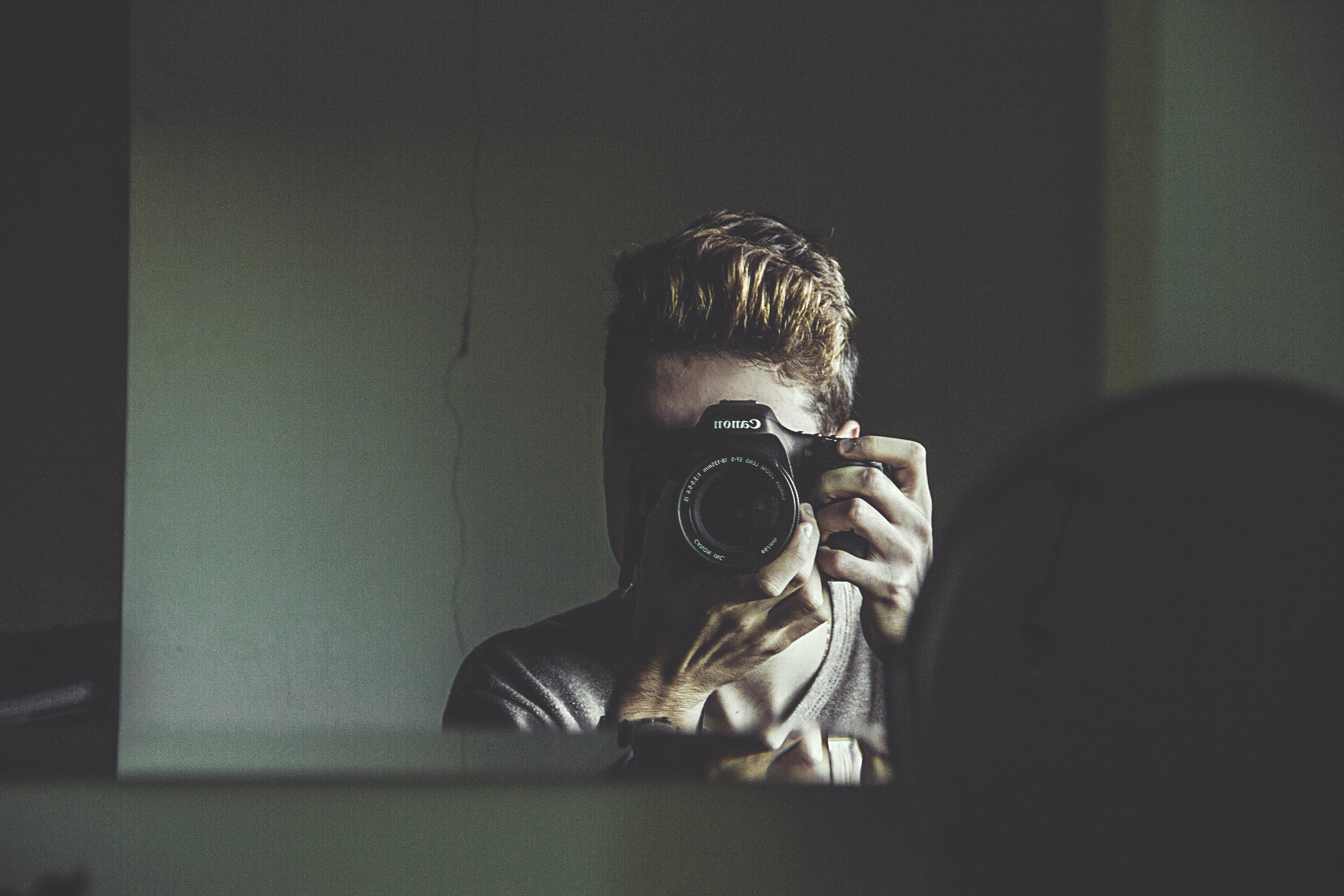 man taking photo on mirror