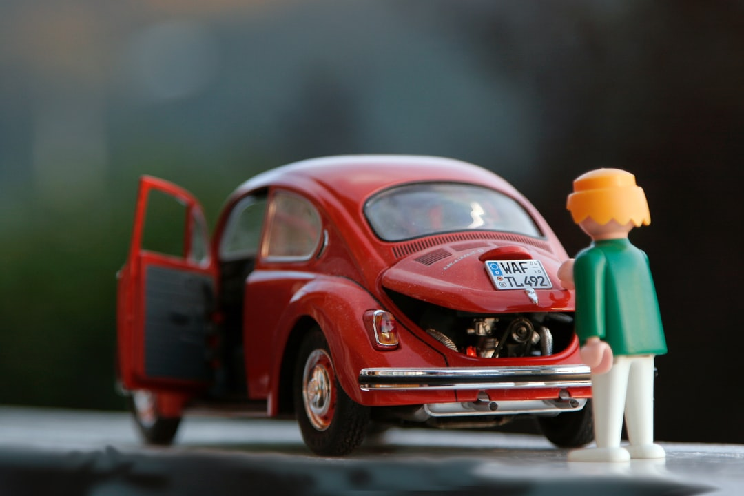 Playmobil toy red beetle with a woman pretending to go into the trunk