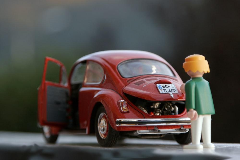 orange hair Lego toy looking at red beetle car