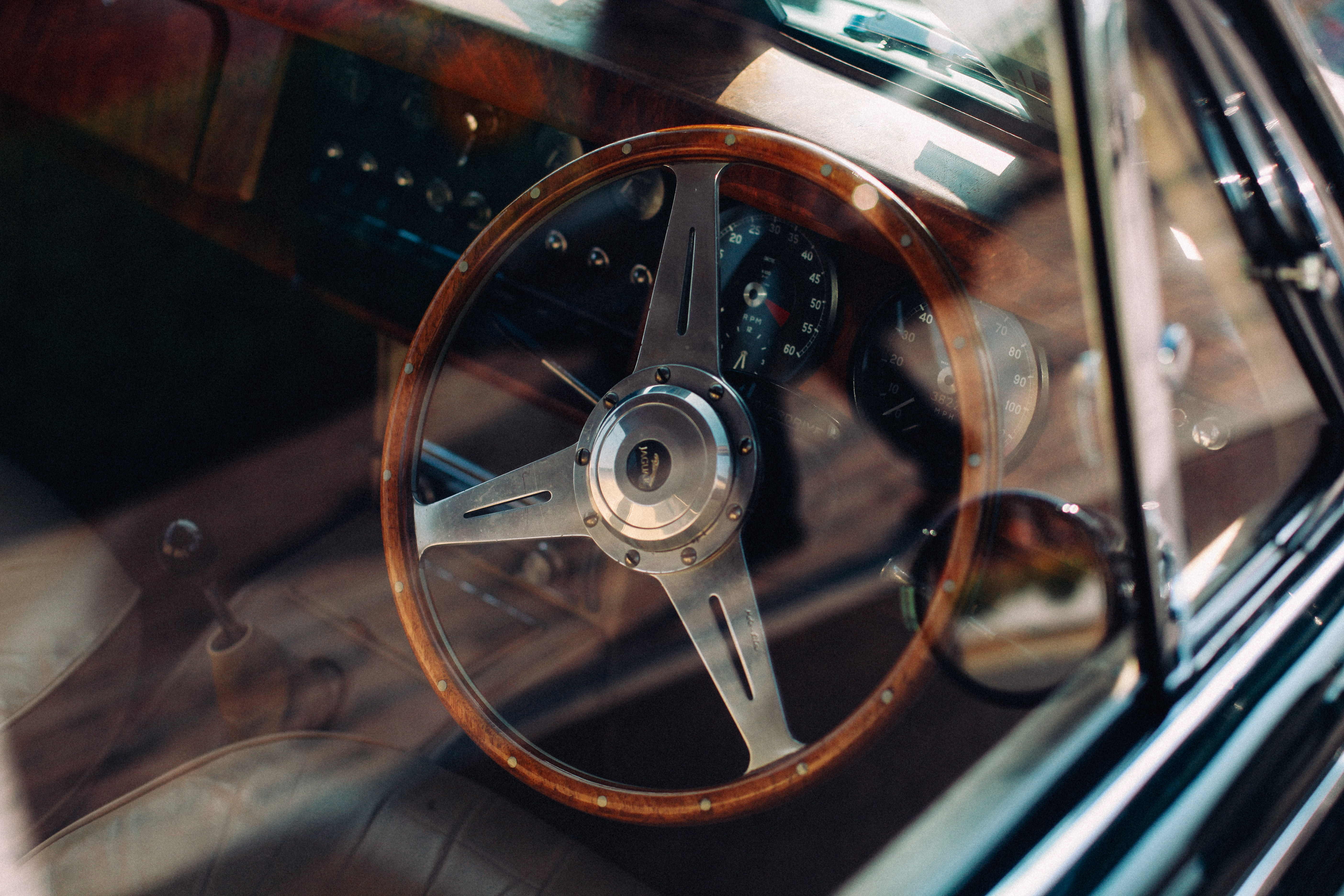 Vintage car interior with wooden steering wheel and window with reflection in London