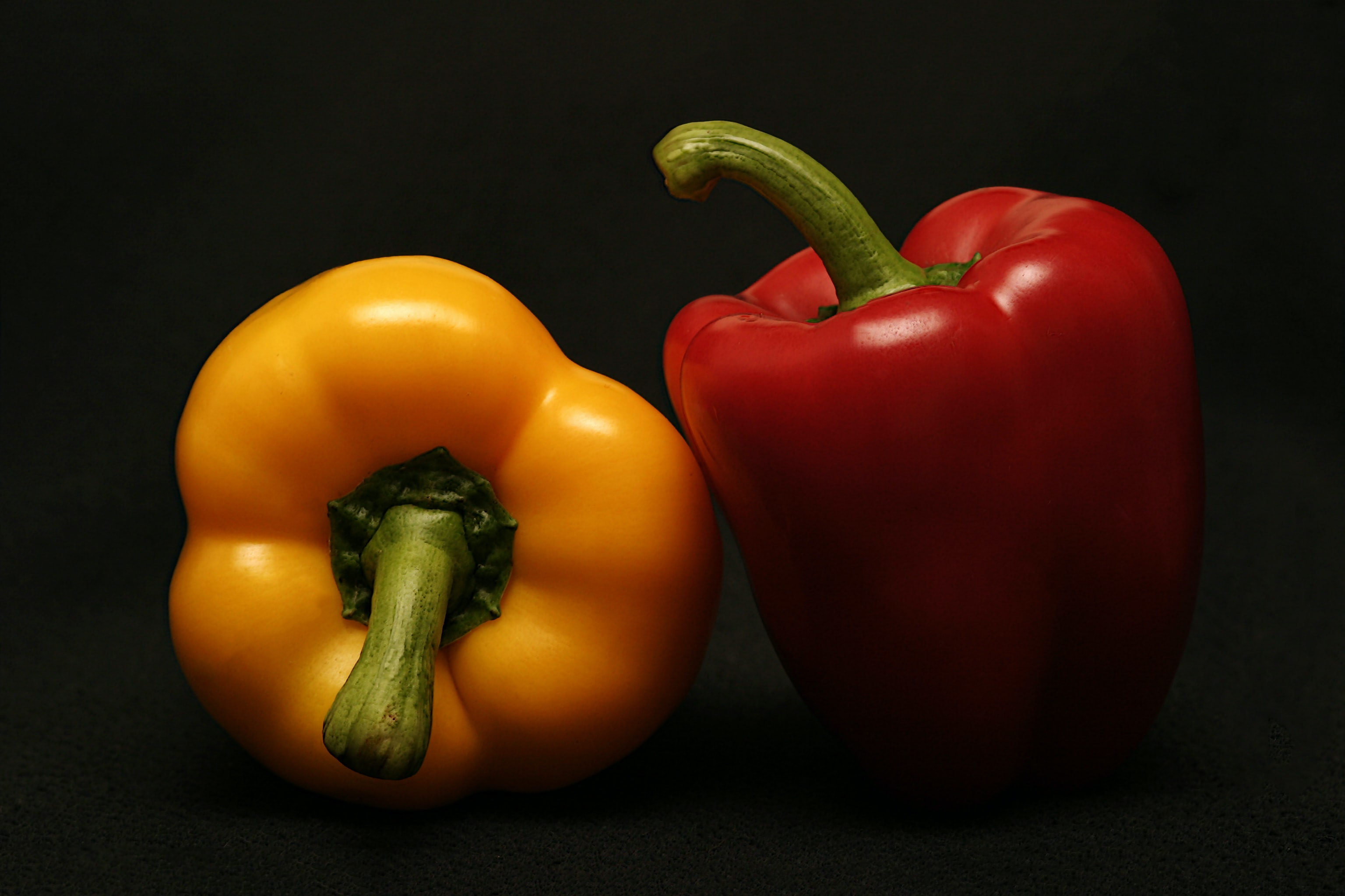 Red and yellow bell peppers in the shadows against a black background