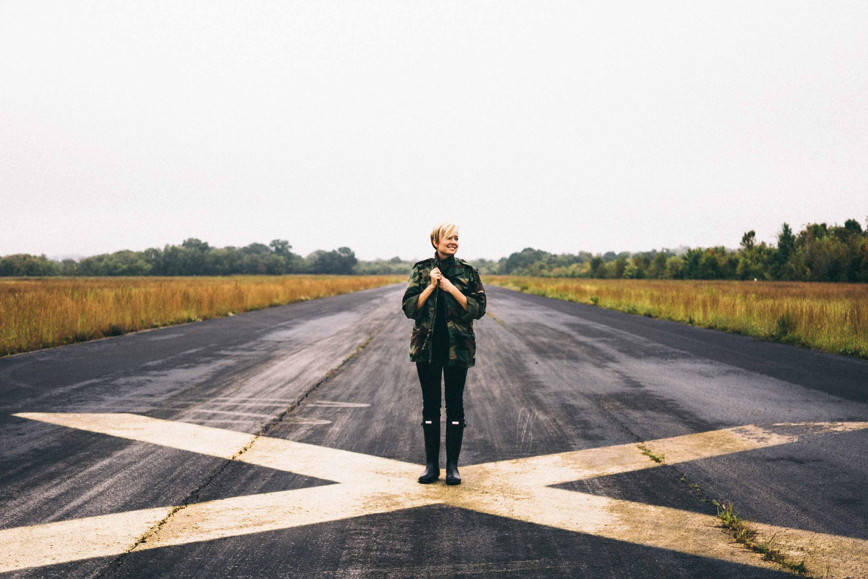 woman standing on black asphalt between green grass under clear blue sky during daytime
