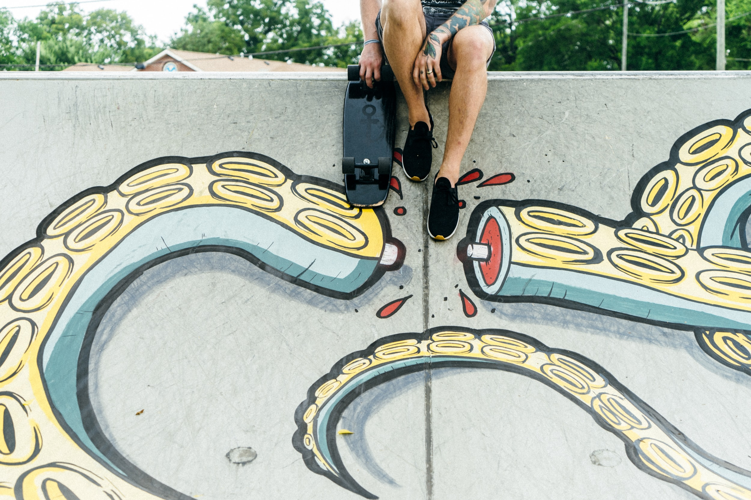 Skateboarder perched on a wall painted with graffiti of an octopus tentacle at Salemtown Board Co