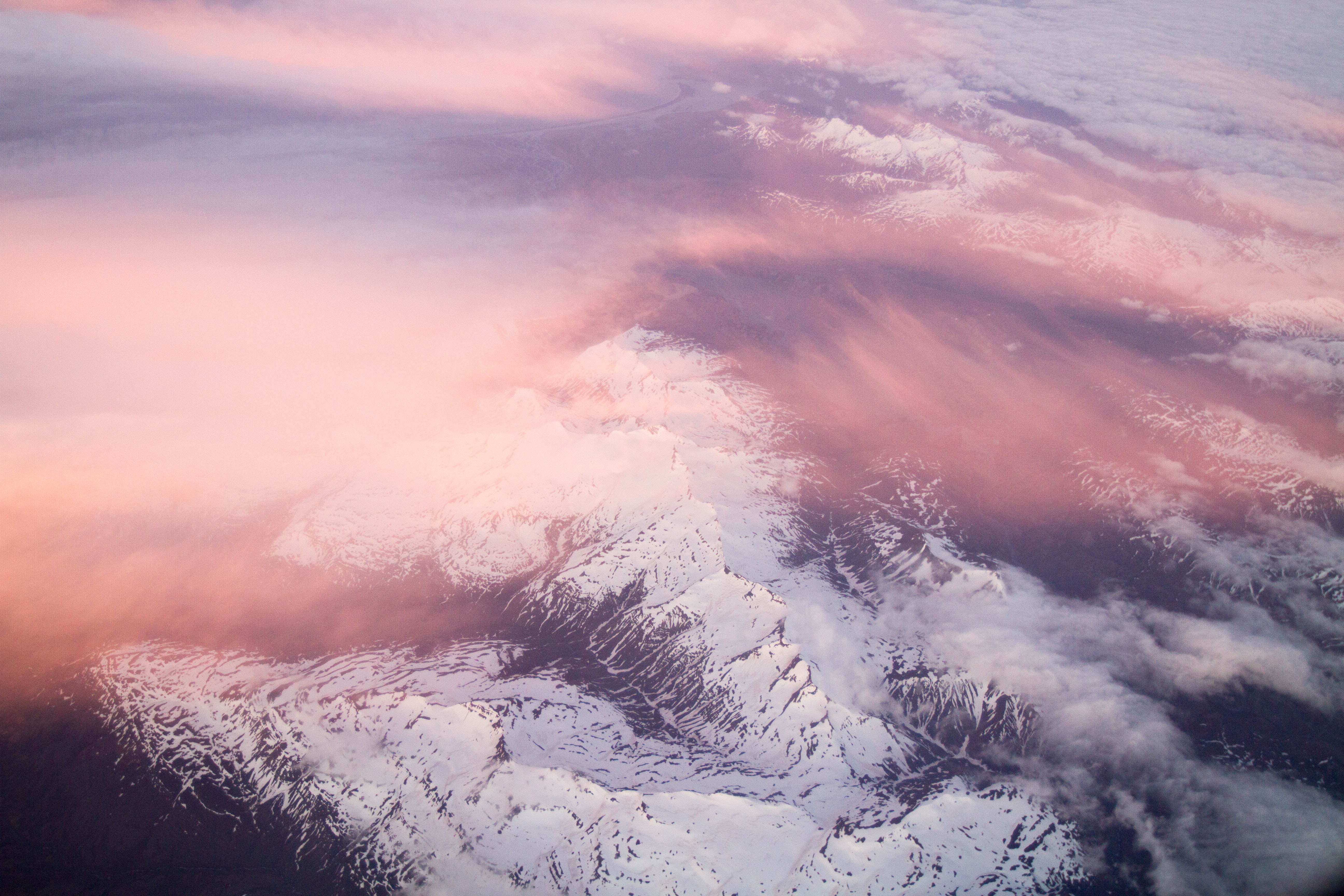 An aerial shot of clouds over white mountain ridges illuminated by the setting sun