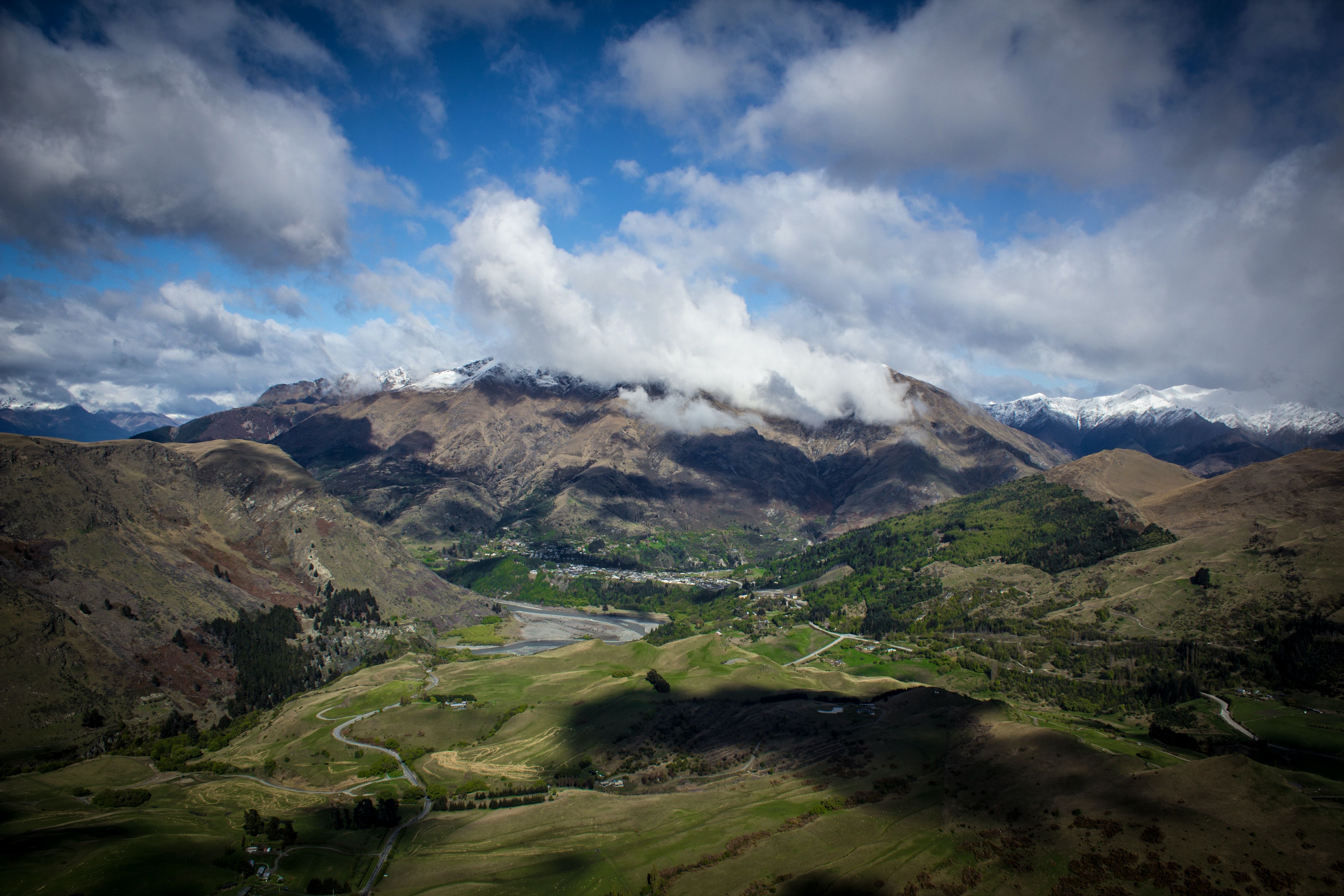 A breathtaking landscape with green plains stretching at the foot of cloud-shrouded mountains