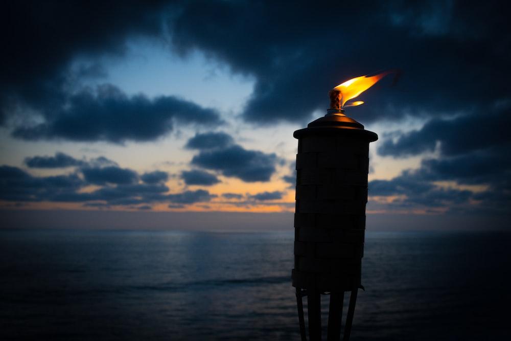 lighted tiki torch near sea at night