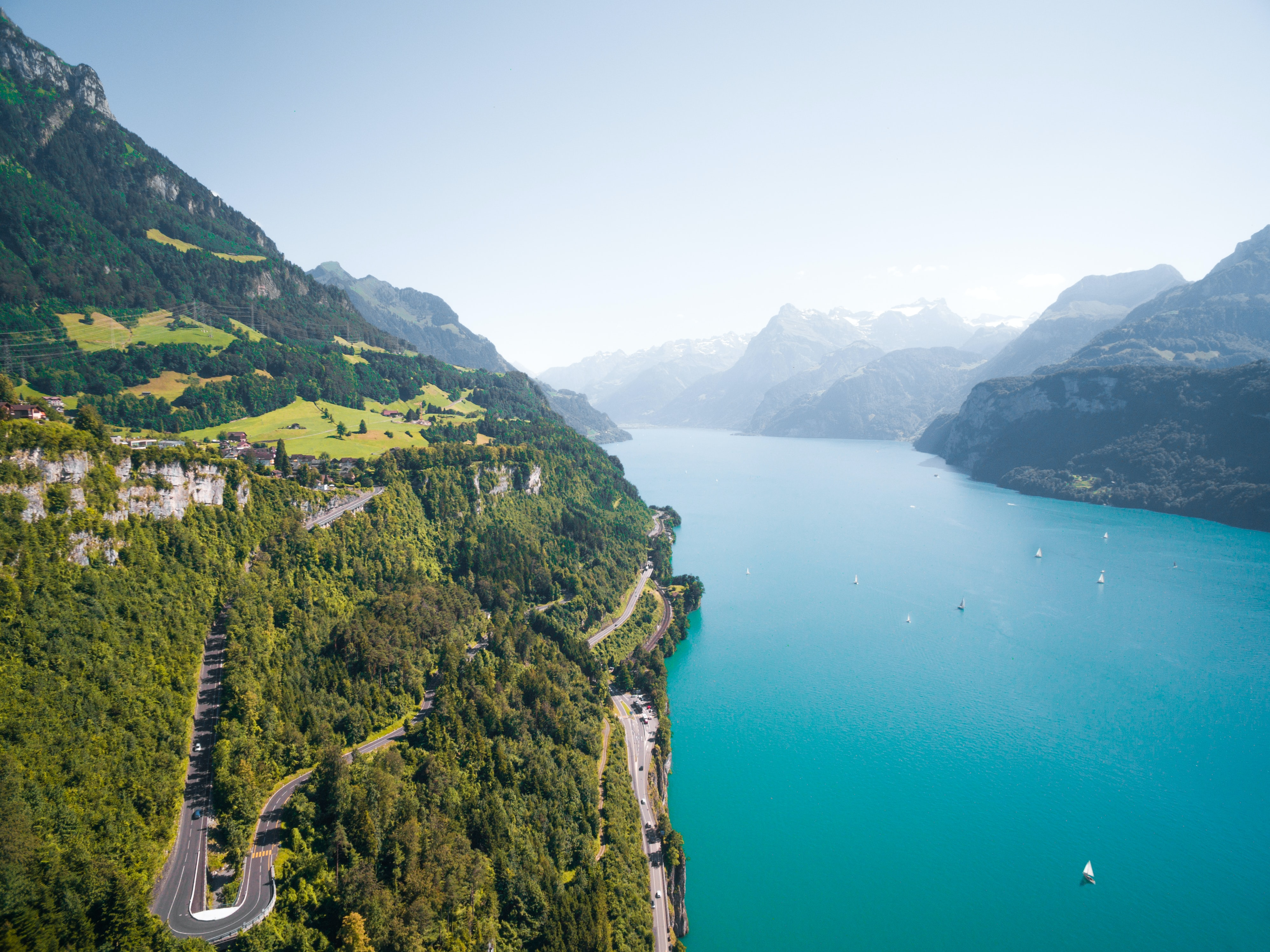 Aerial view of long roads carved in a green cliff overlooking an azure Alpine river