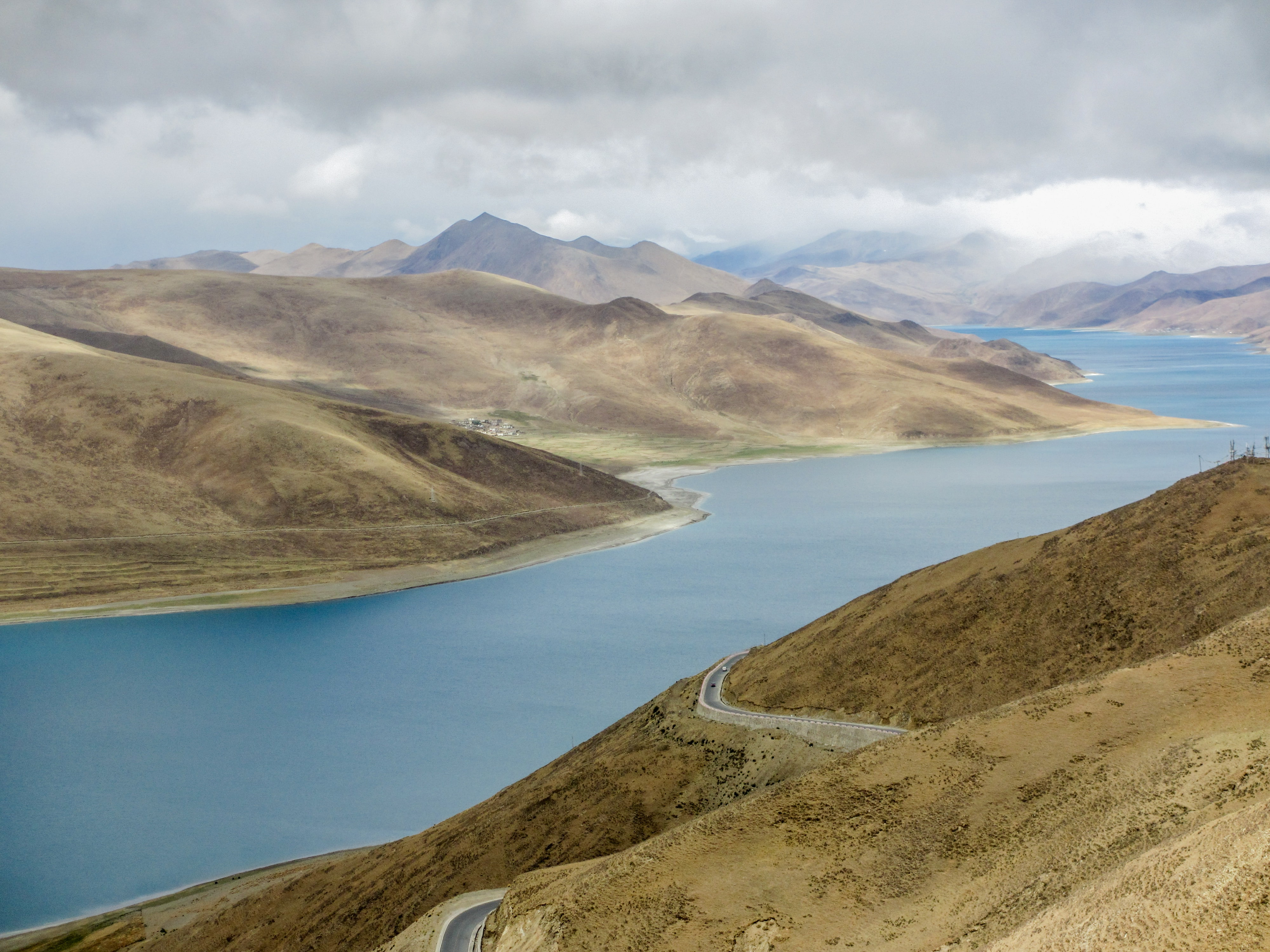 A river flowing between dry hilly banks in Tibet