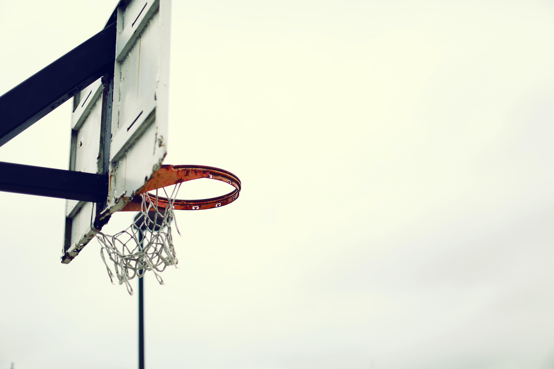A shot from below a basketball backboard in an outdoor court