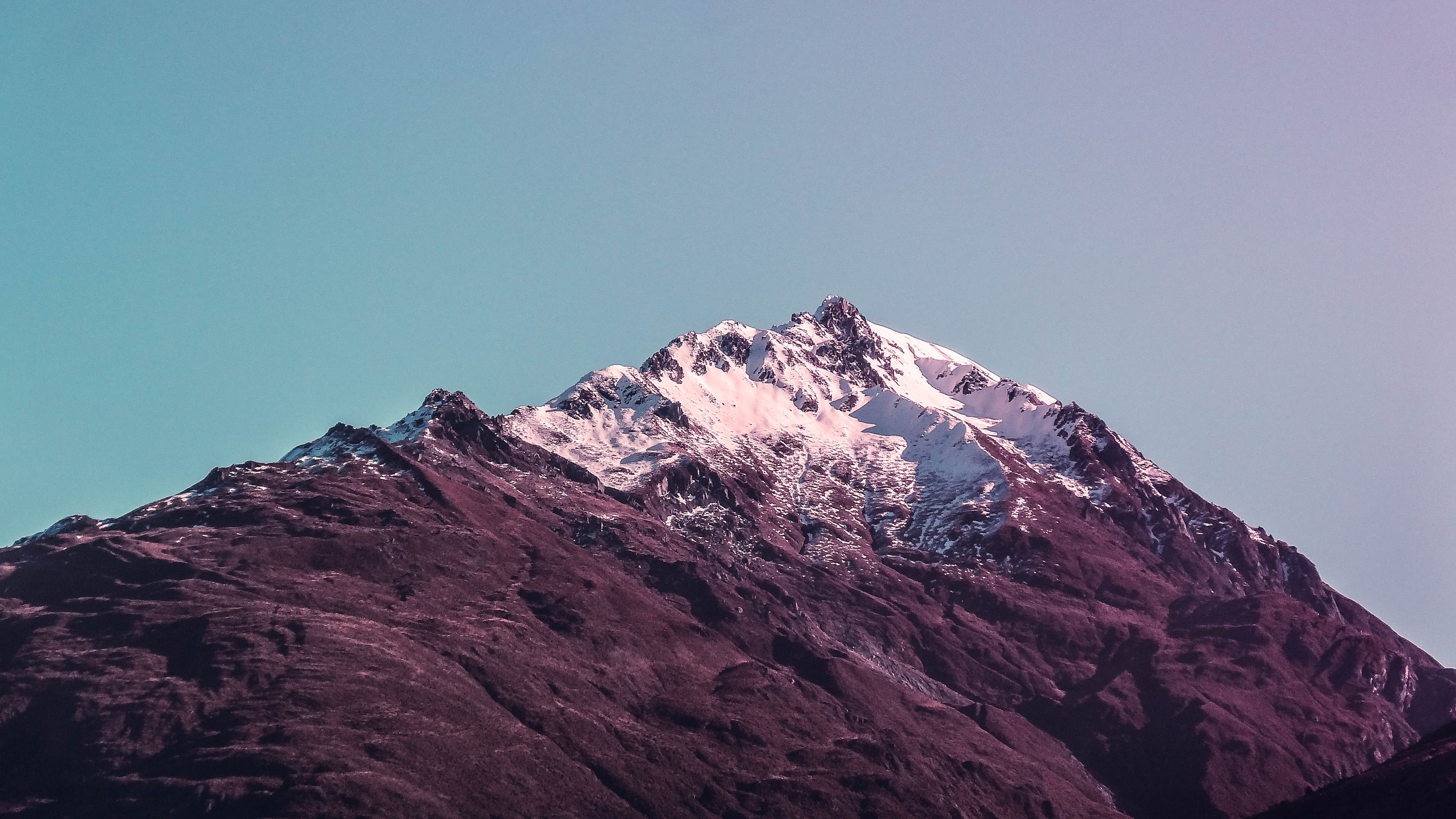 A purple-hued shot of a large snow-capped mountain peak