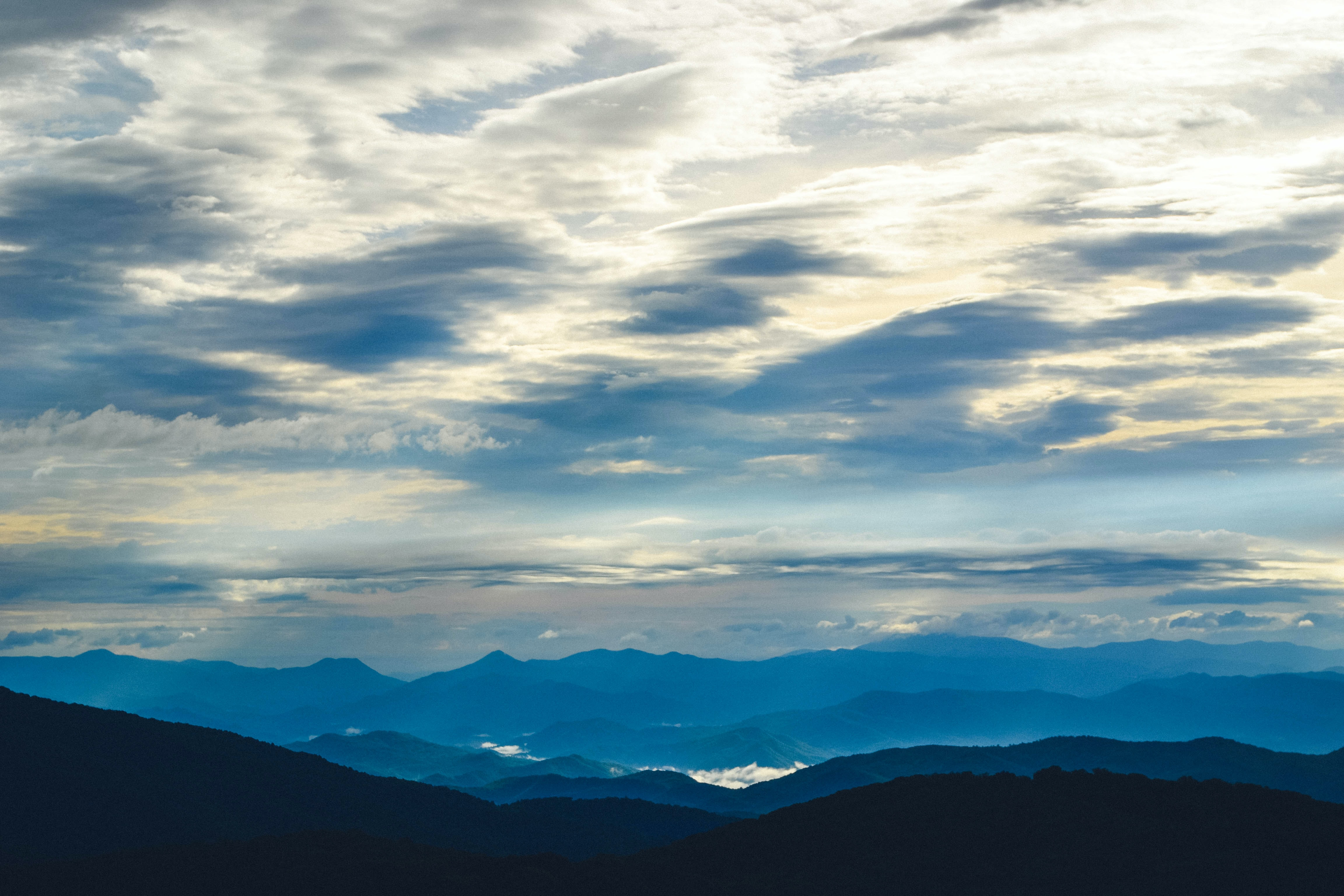 Panoramic shot of blue mountain ranges and cloudy skies.