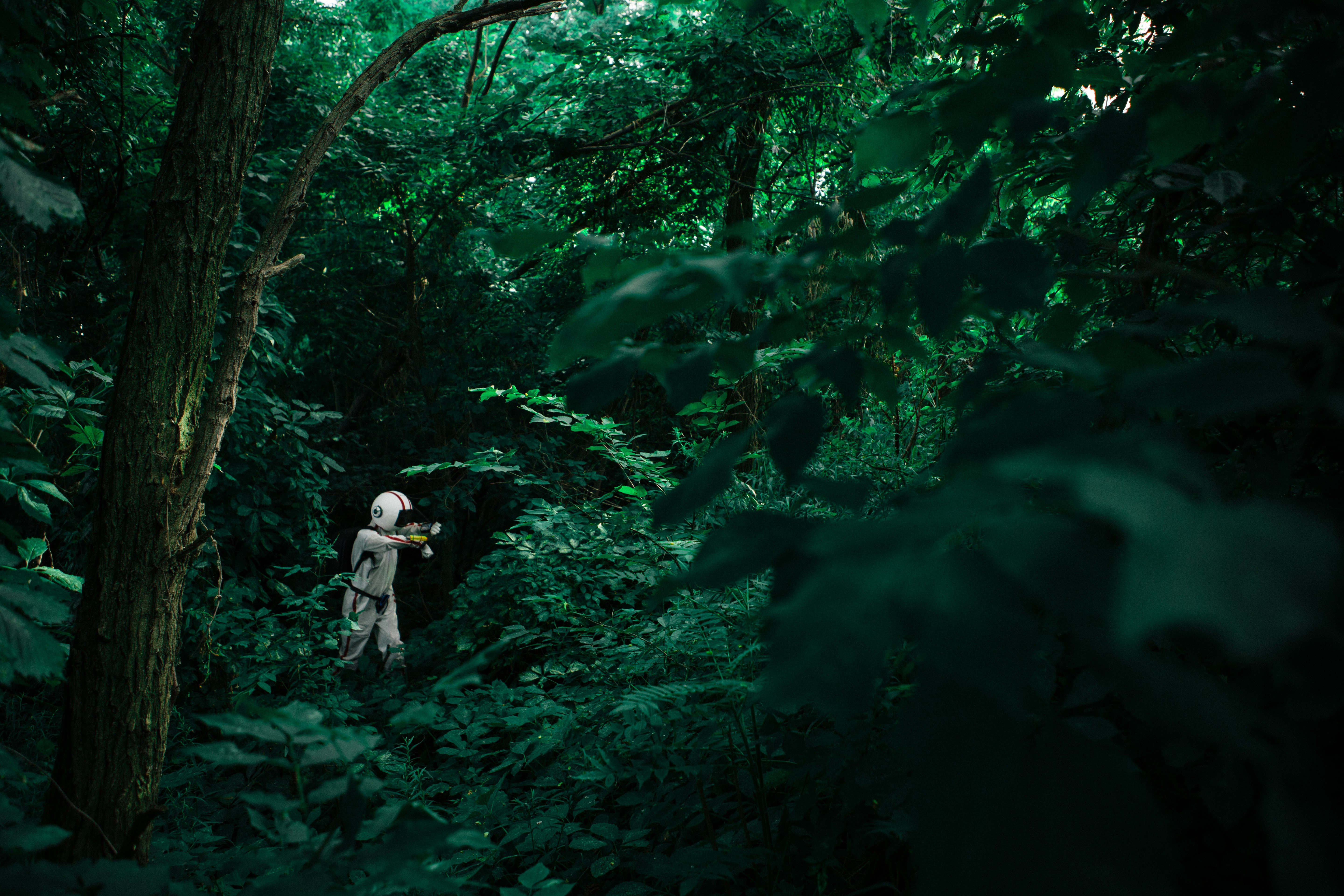 A person dressed in an other-worldly space suit surrounded by verdant forest vegetation on Nun's Island