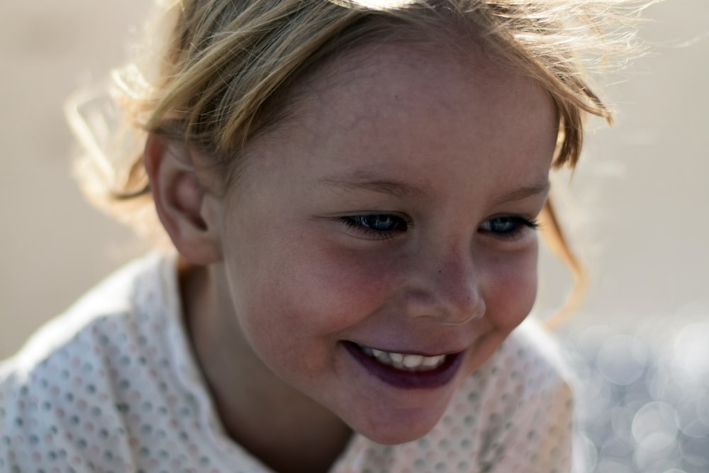 selective focus photo of young smiling girl