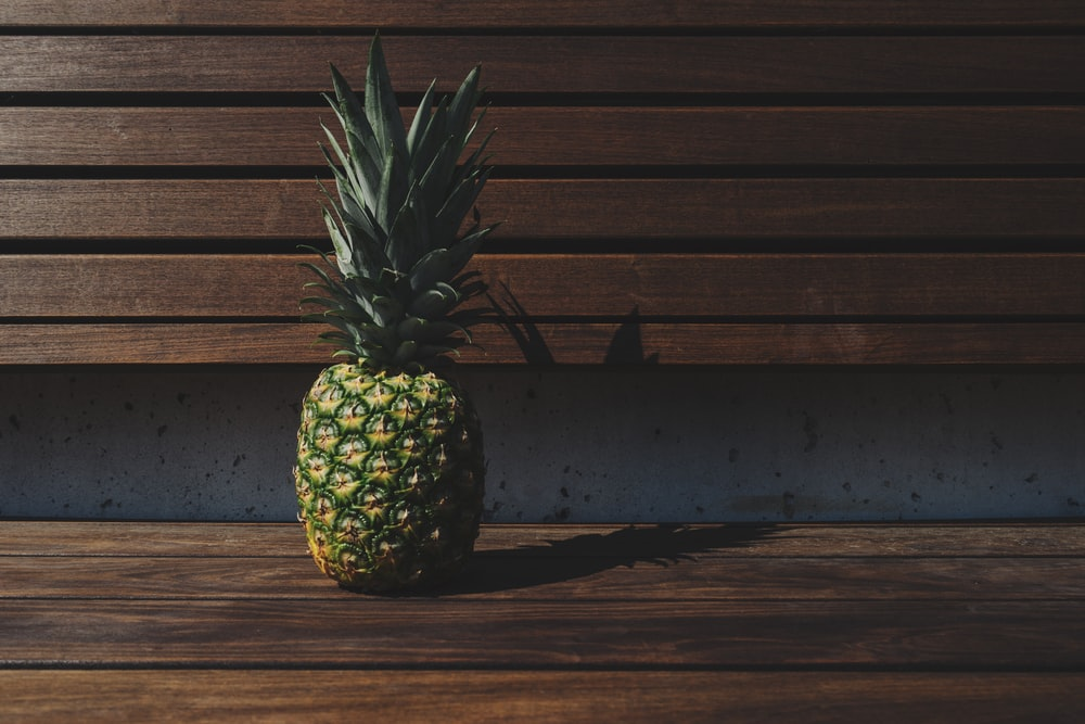 green and yellow pineapple placed on brown wooden pallet bench