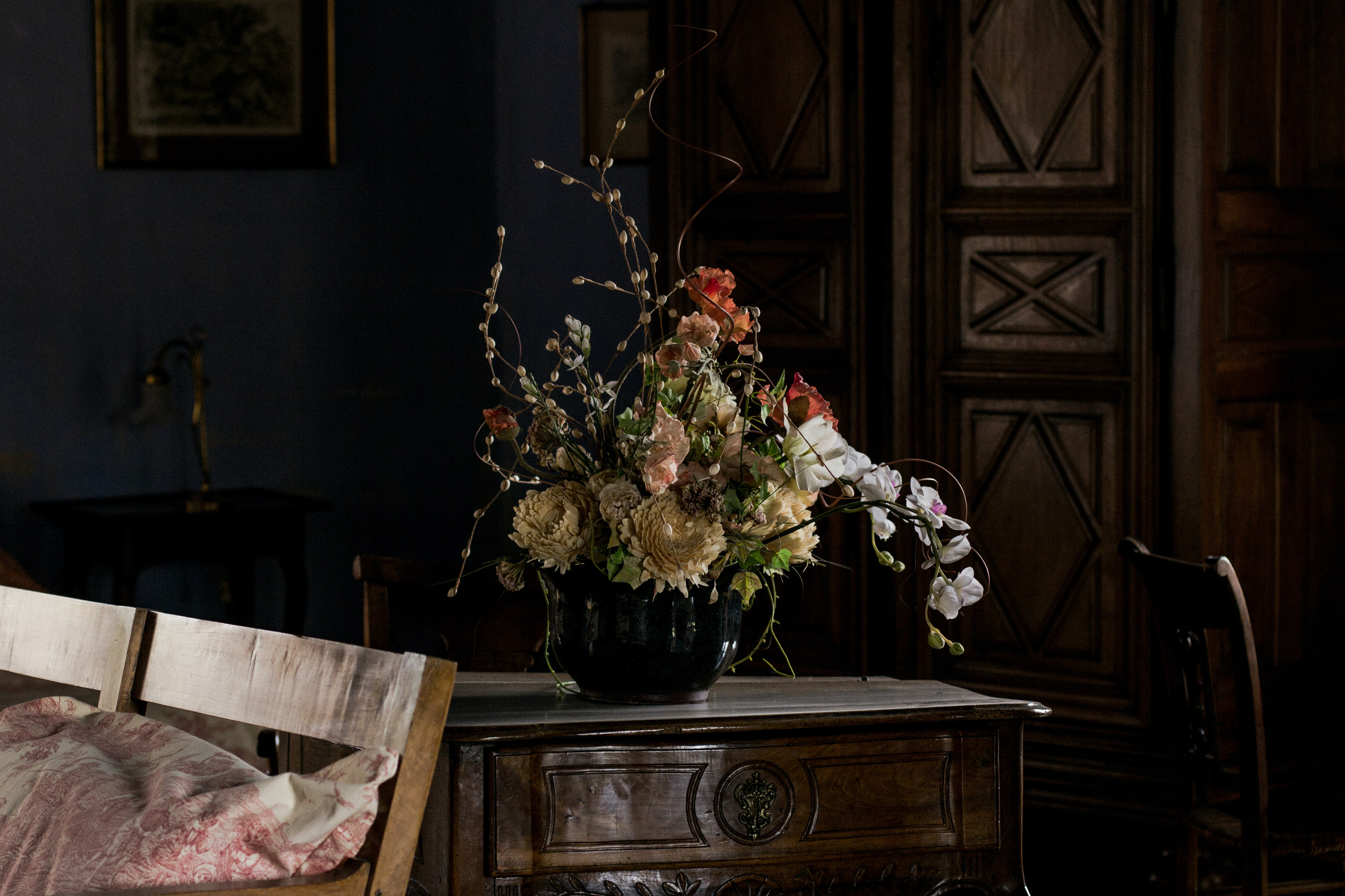 A black vase with various kinds of flowers and catkins on an elegant wooden cabinet