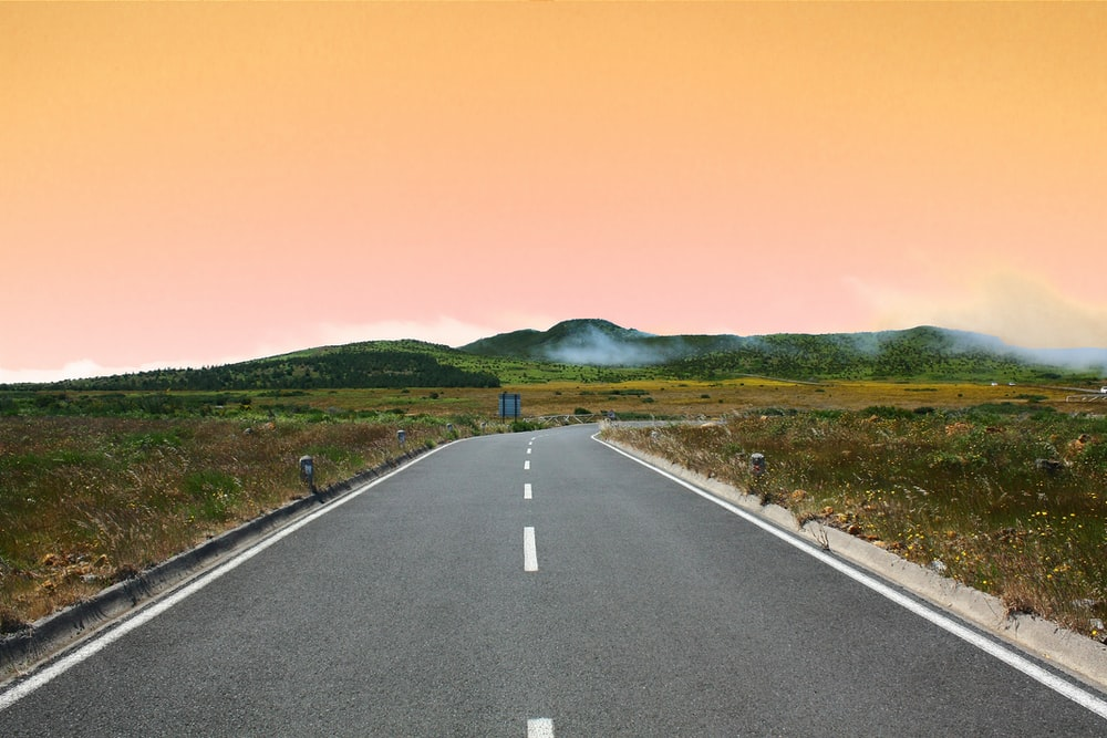 gray concrete road under orange cloudy sky during daytime